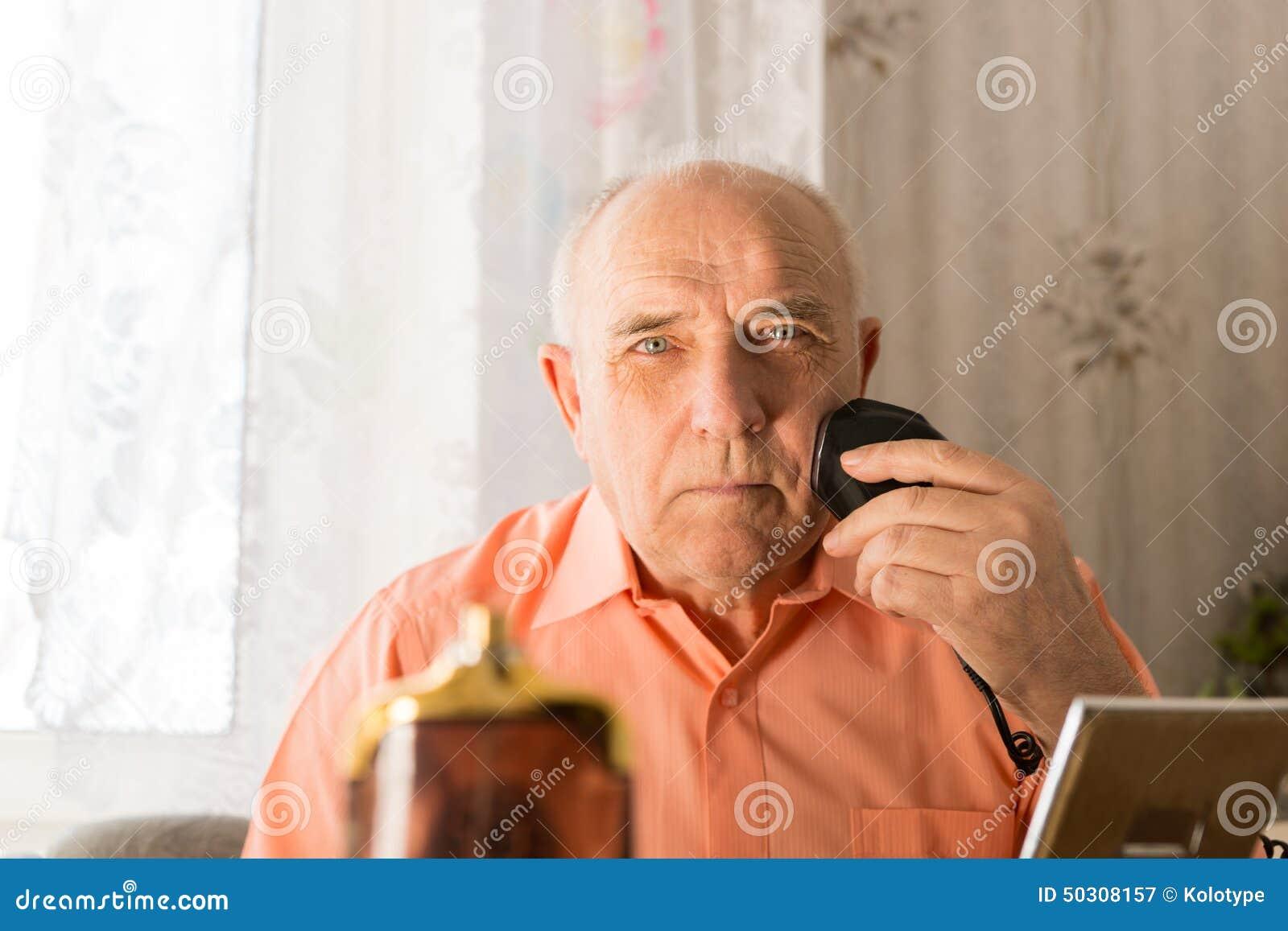 刮在面孔的老人头发与电剃刀图片