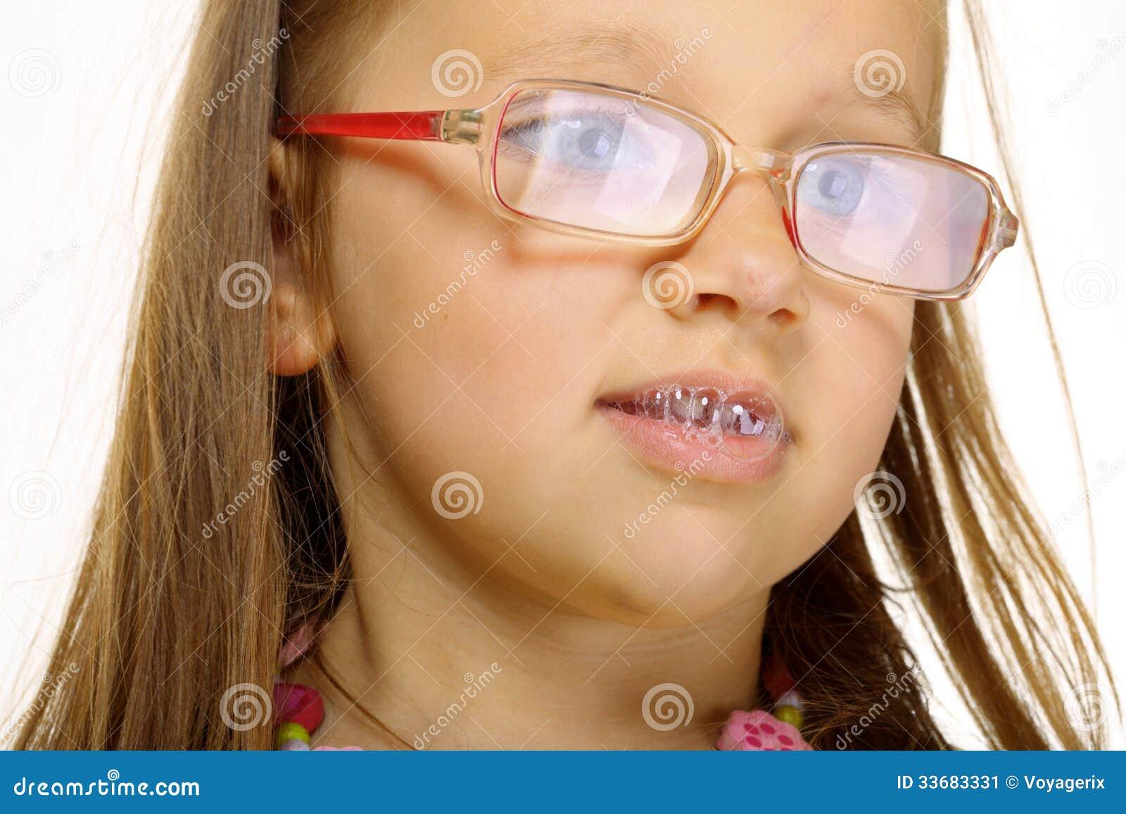 关闭做乐趣唾液泡影的玻璃的小女孩