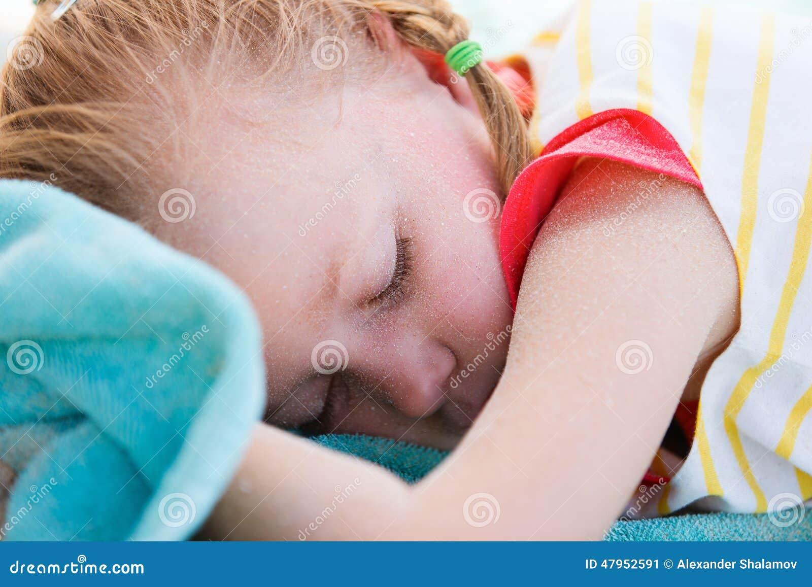 海滩睡觉的可爱的小女孩