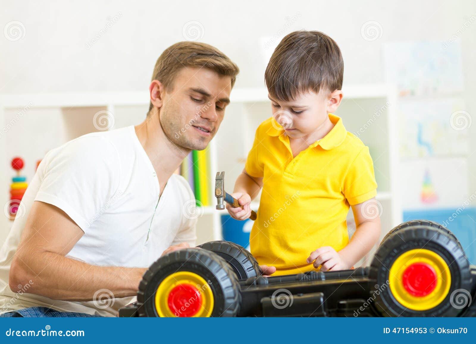 孩子男孩和爸爸修理玩具汽车.
