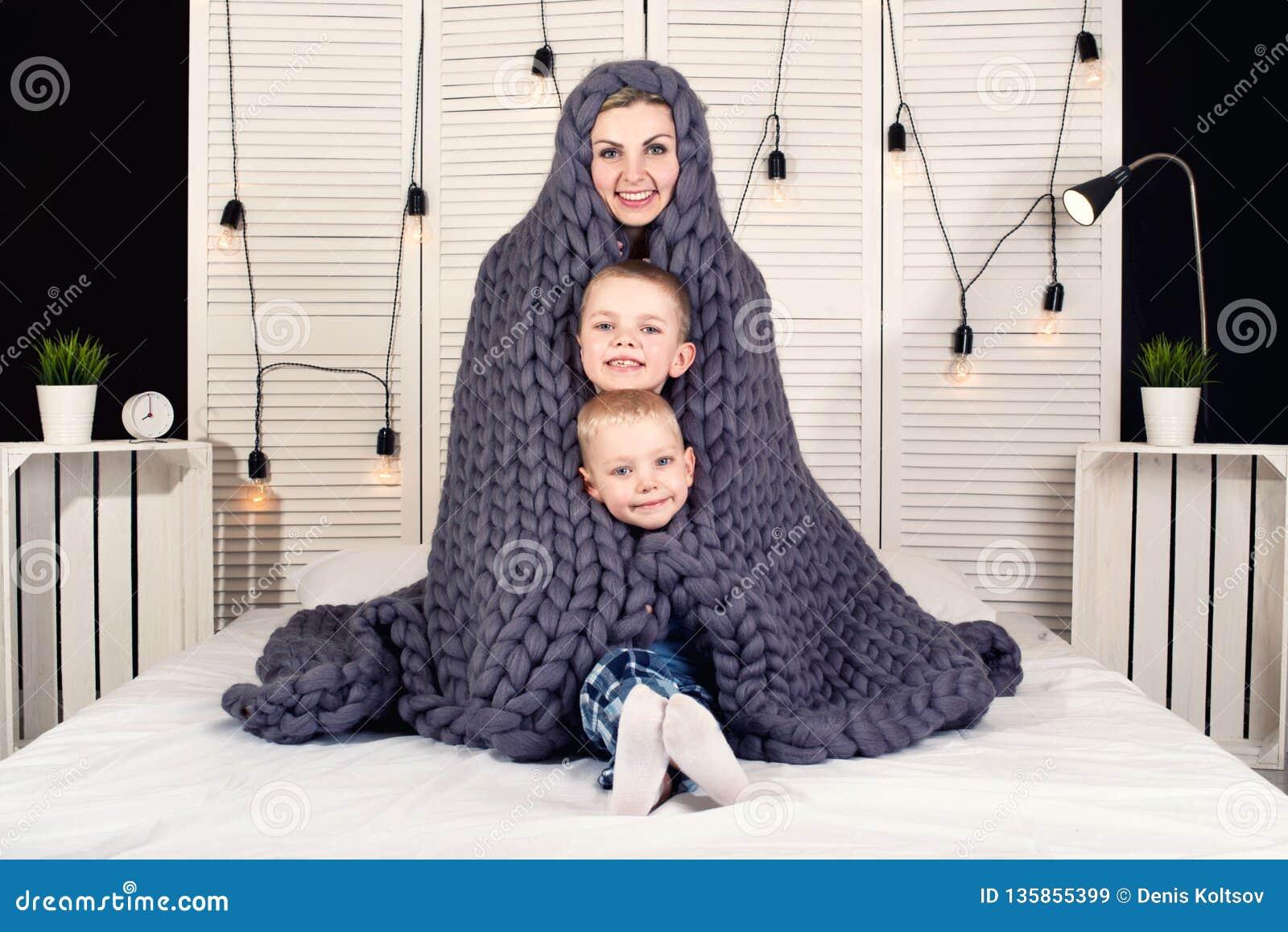 ¡Buenos días! La madre y dos pequeños hijos ocultan debajo de una manta hecha punto El despertar positivo