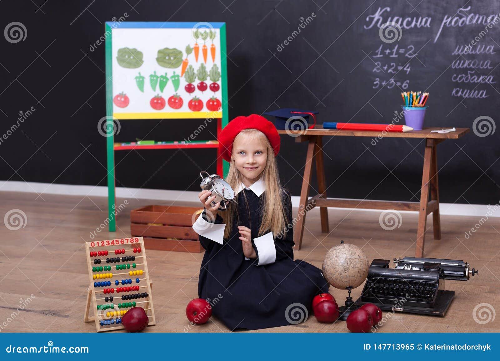 ¡De nuevo a escuela! La colegiala se sienta en una lección con un reloj en sus manos Concepto de la escuela En la pizarra en la l