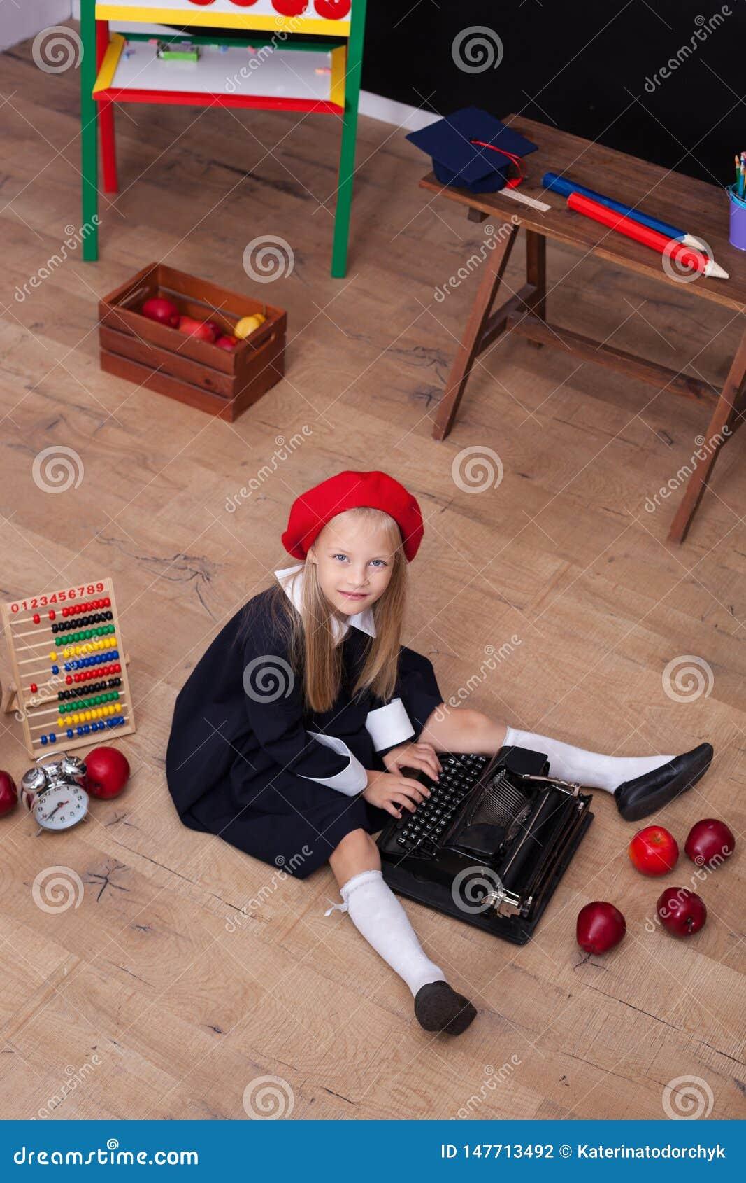 ¡De nuevo a escuela! La muchacha en la boina se sienta con una máquina de escribir y aprende en clase En la pizarra en la lengua