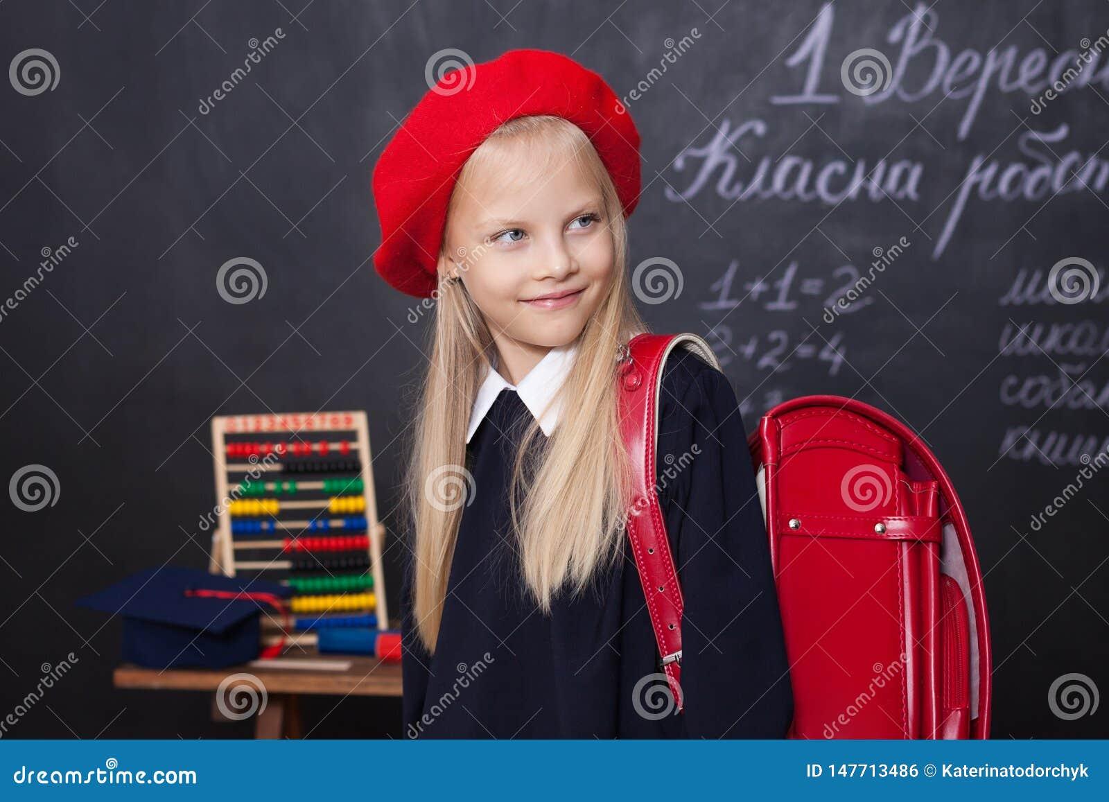 ¡De nuevo a escuela! La niña se coloca en escuela con una mochila roja La colegiala responde a la lección El niño está estudiando