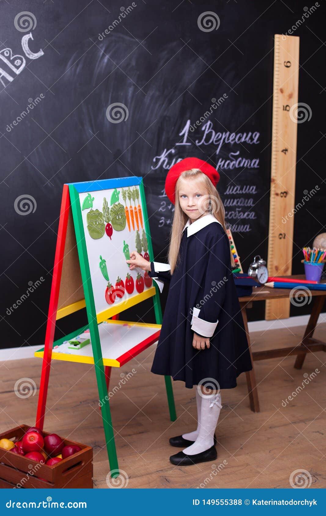 ¡De nuevo a escuela! la niña se está colocando cerca del consejo escolar En la pizarra en ucraniano se escribe el ?1 de septiembr