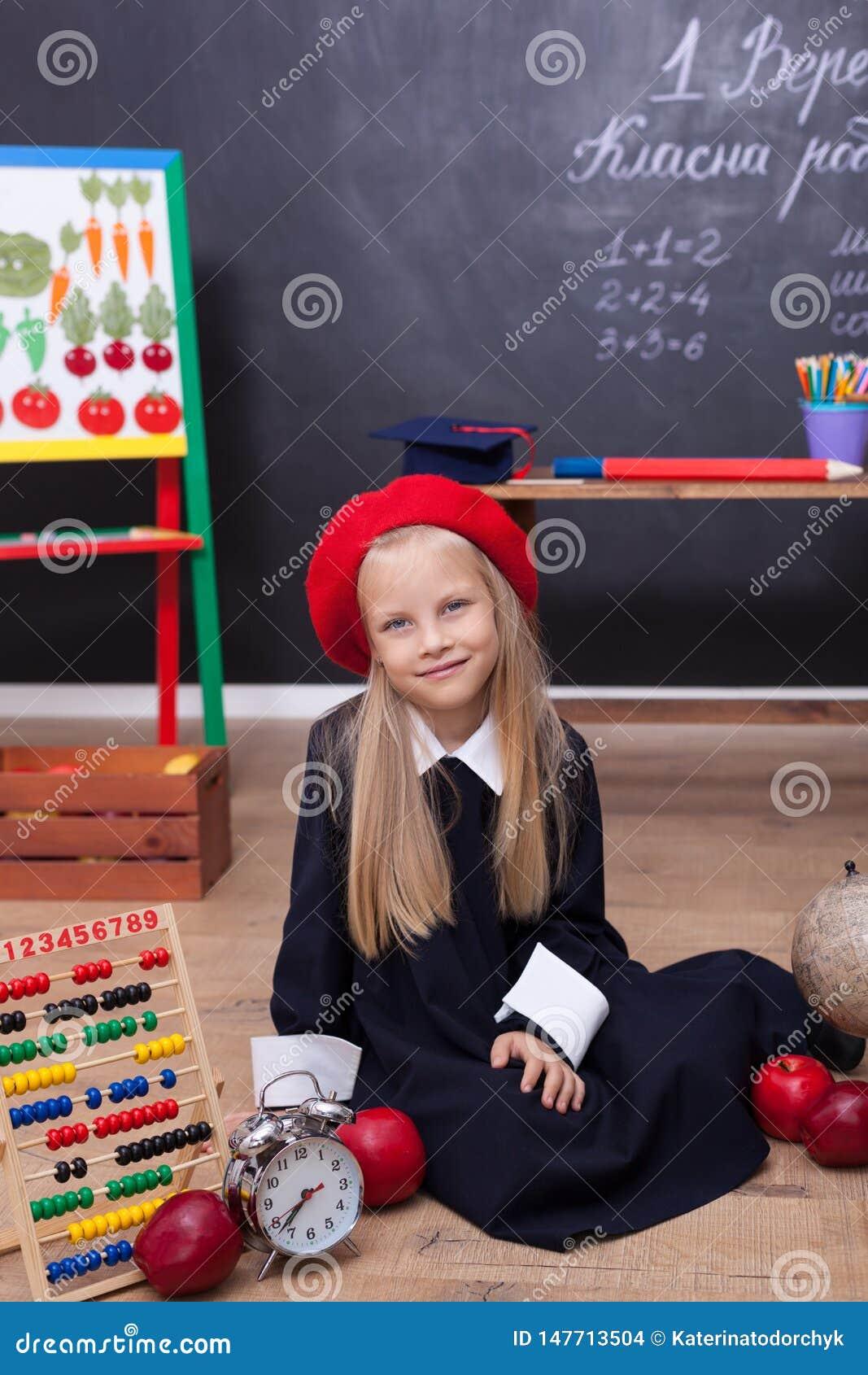 ¡De nuevo a escuela! Una muchacha en el uniforme escolar que se sienta en una lección Responde a la lección En la pizarra en la l