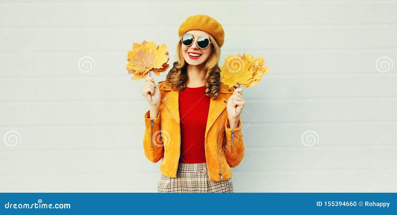 ¡Estación del otoño! Mujer sonriente feliz elegante con las hojas de arce amarillas en la boina francesa que presenta sobre la pa