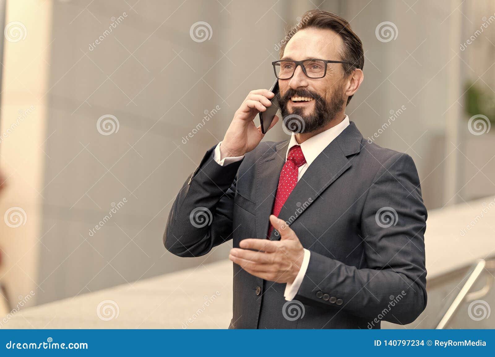 ¡Mucho! El hombre de negocios barbudo habla por el teléfono y ríe Opinión un hombre de negocios atractivo joven en vidrios usando