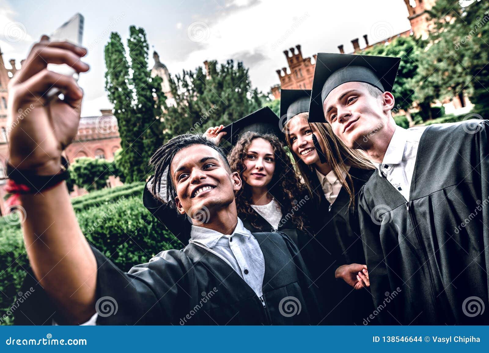 ¡Nosotros ` VE finalmente graduado! Los graduados felices se están colocando en la universidad al aire libre en capas que sonríen