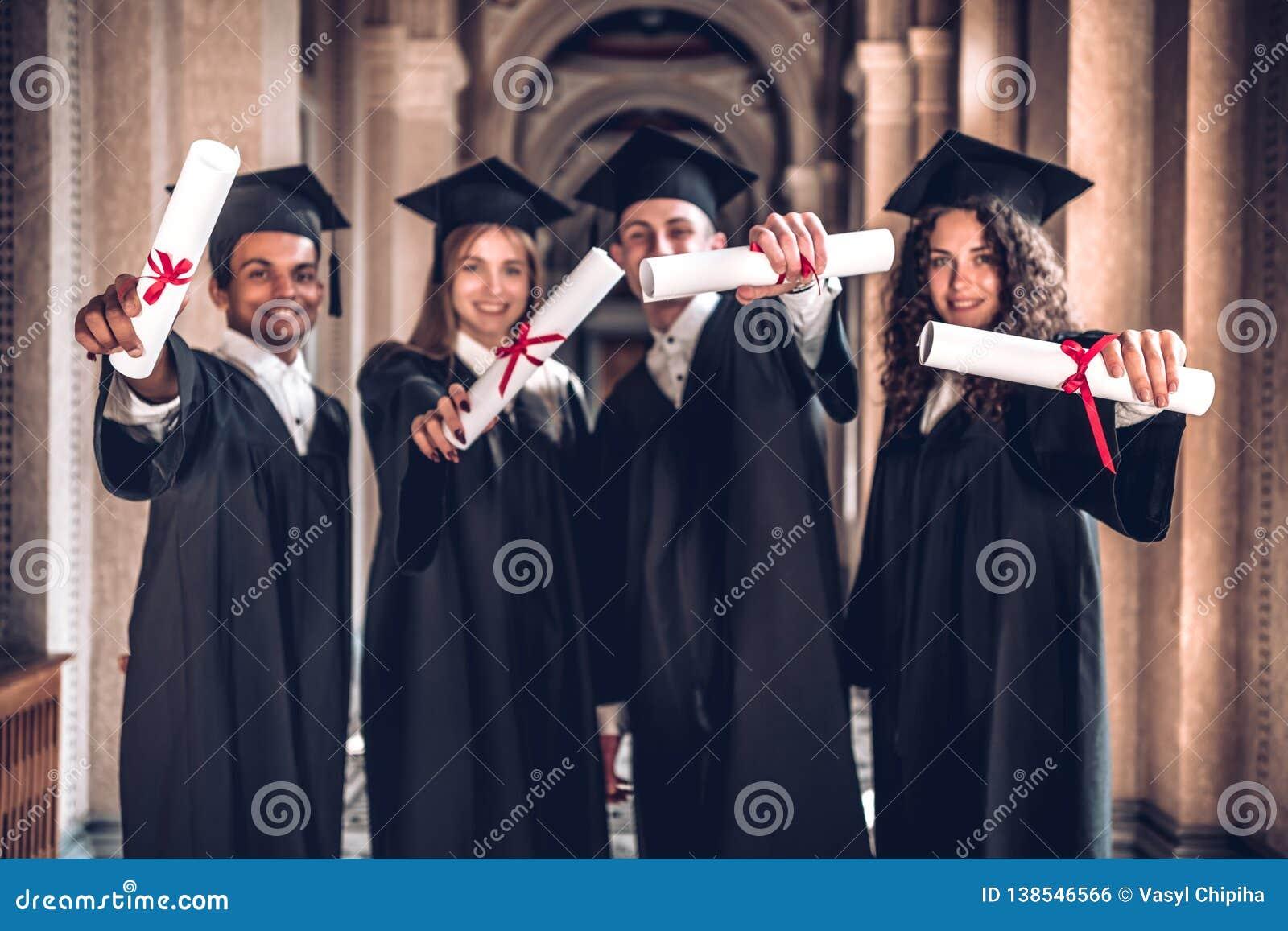 ¡Trabajamos difícilmente y conseguimos resultados! Grupo de graduados sonrientes que muestran sus diplomas, uniéndose en pasillo