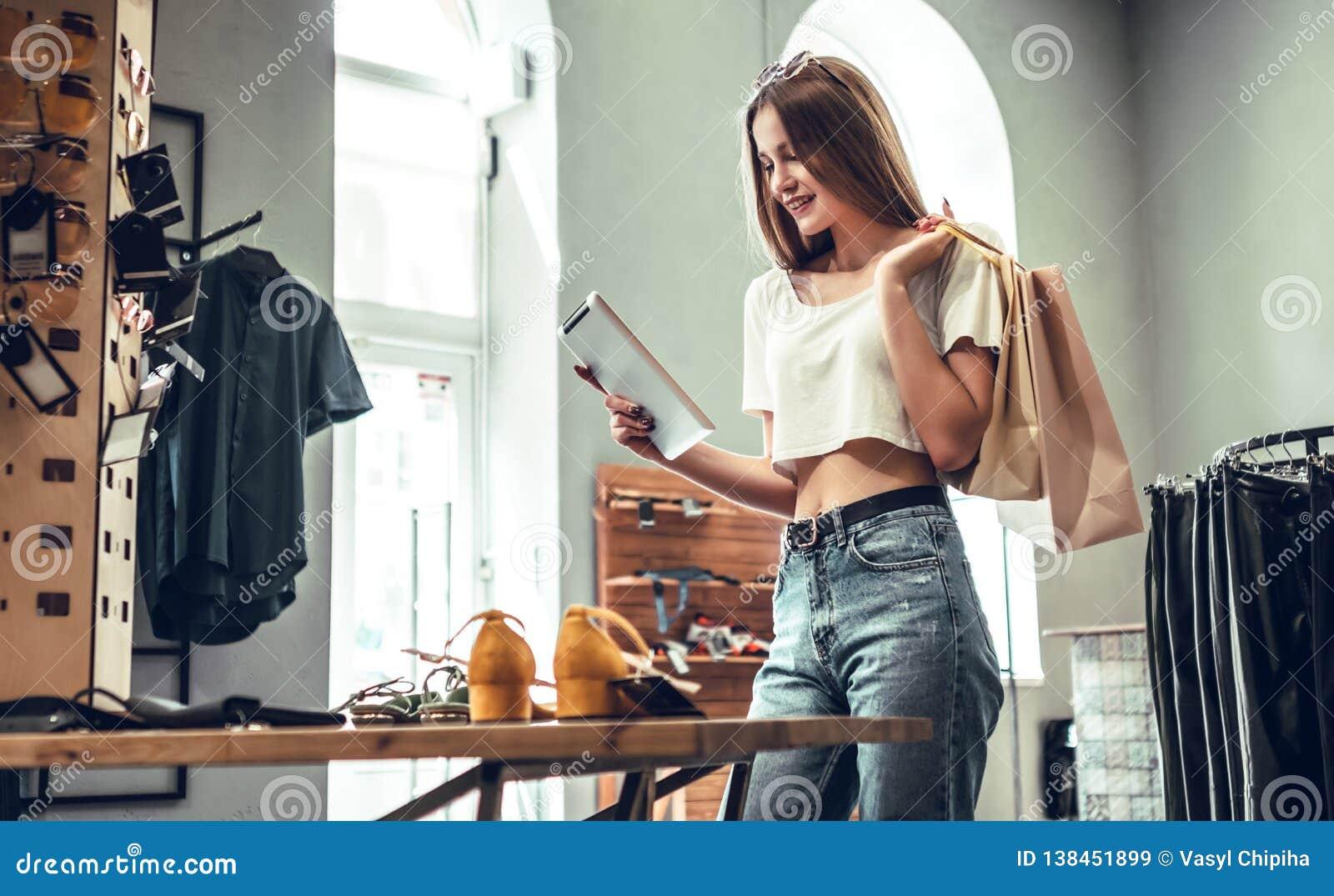¿Compras en línea o no? Mujer hermosa con la tableta digital en la tienda La morenita de moda en ropa elegante elige los zapatos