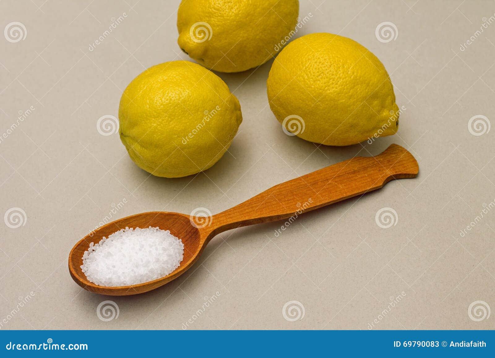 Ácido cítrico en cuchara en el fondo de limones