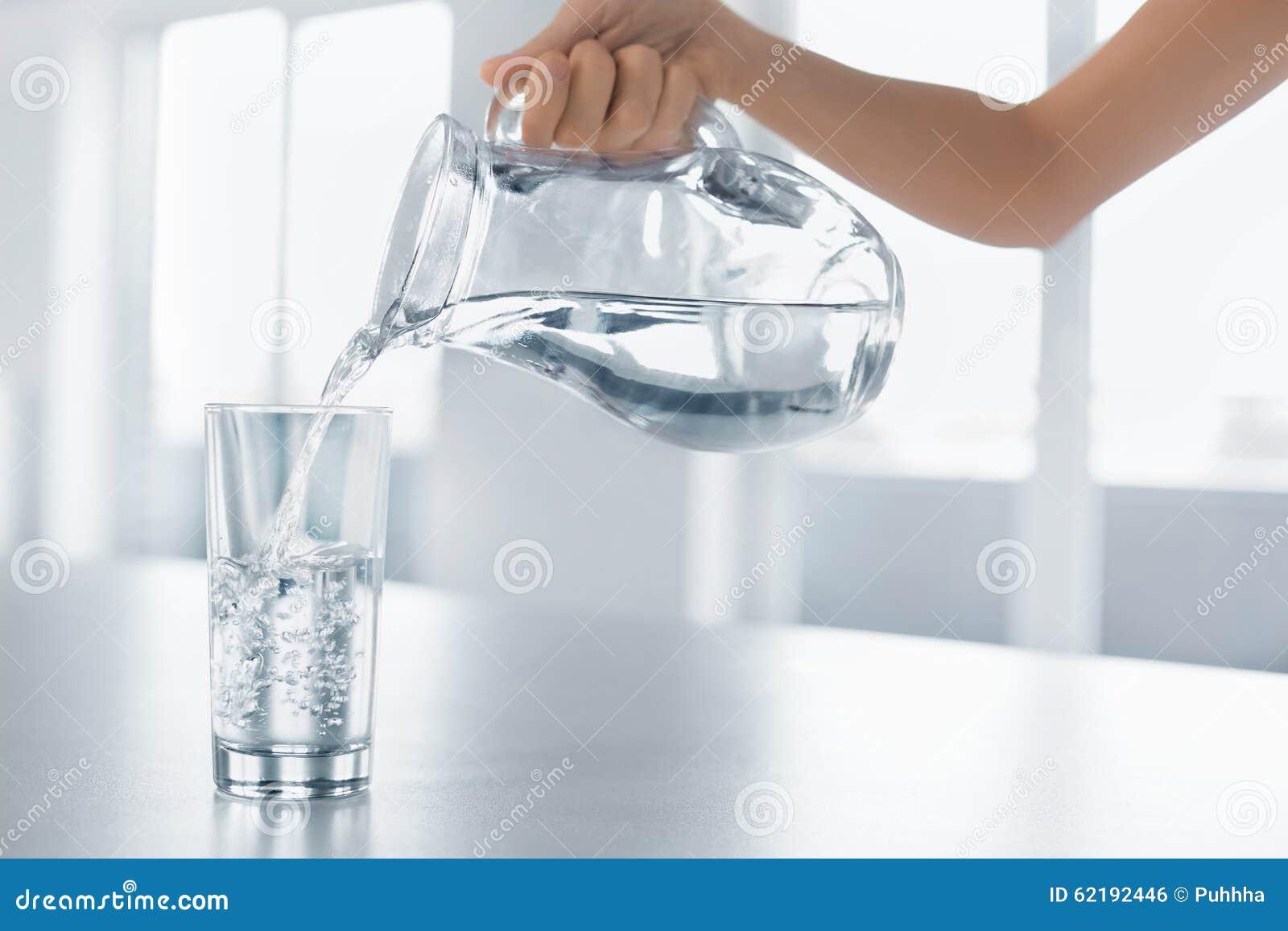 Água da bebida Água de derramamento da mão da mulher do jarro em um Glas