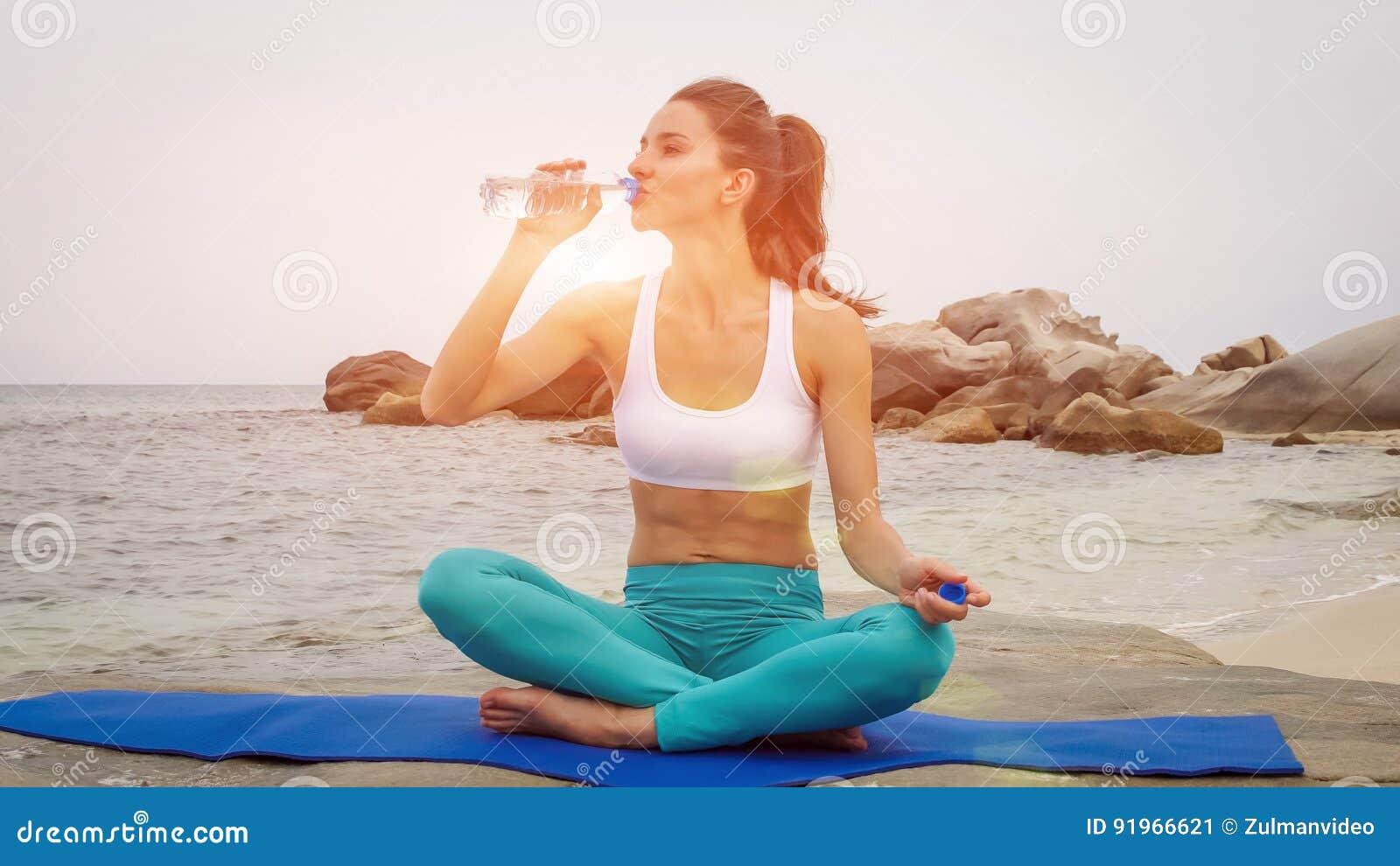 A água da bebida da mulher da aptidão após ter feito o esporte exercita na praia no por do sol