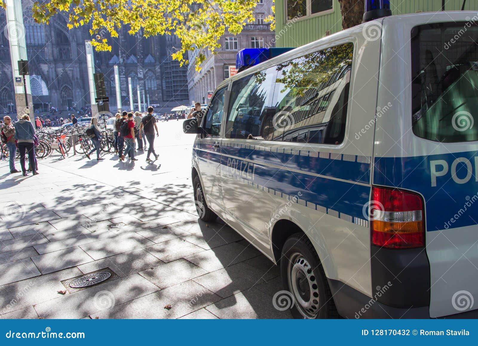ÁGUA DE COLÔNIA, ALEMANHA, EM OUTUBRO DE 2018: Carro e povos de polícia que andam no quadrado na frente da casa do ` s da água de