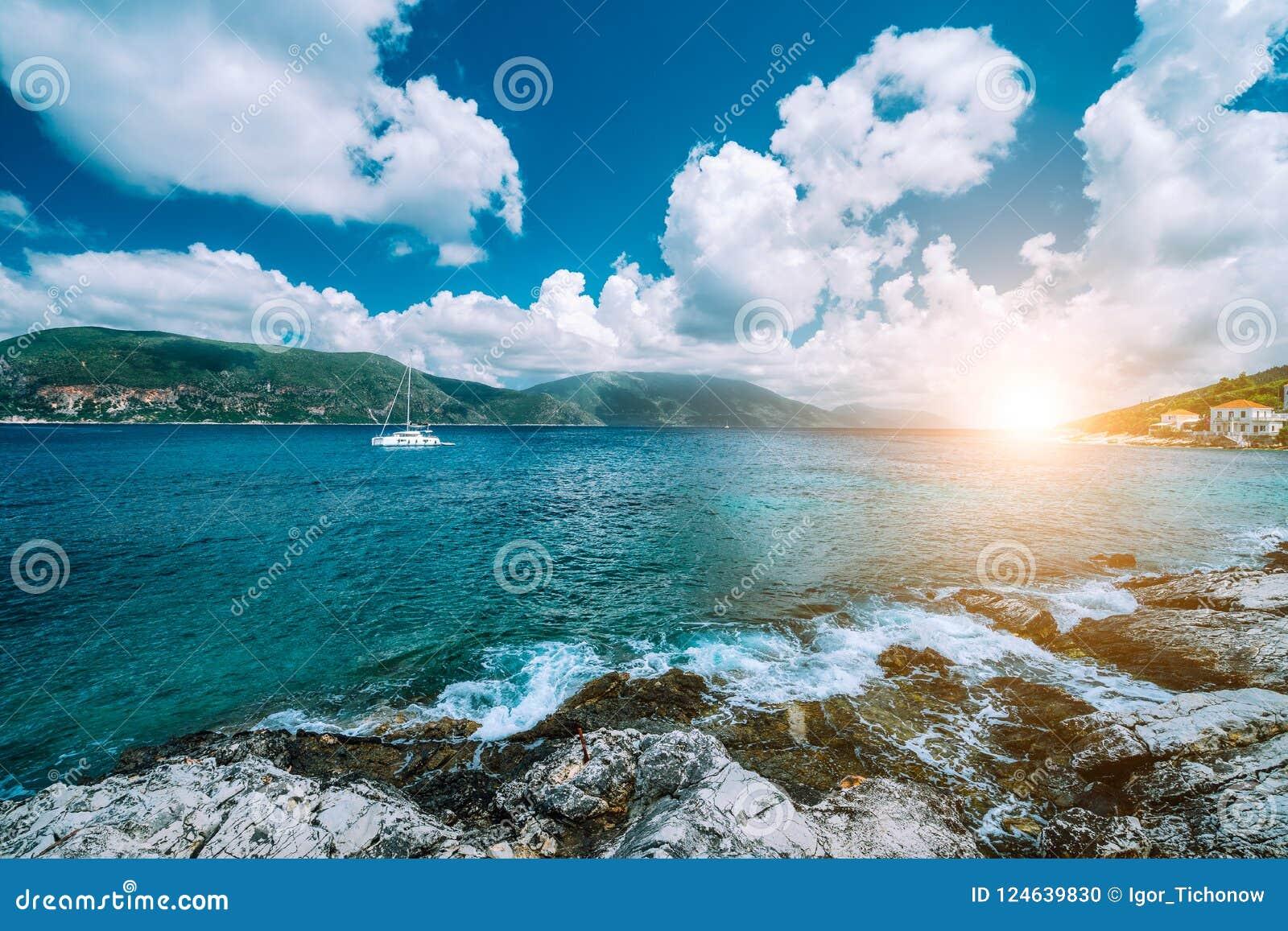 Água de mar Mediterrâneo azul transparente claro da cerceta de turquesa na cidade de Fiskardo Iate branco no mar aberto em