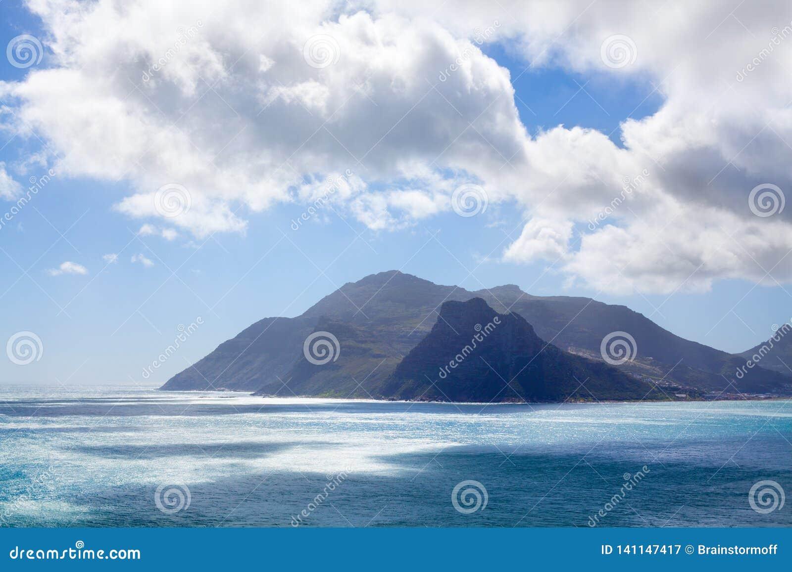 Água do oceano de turquesa do Seascape, céu azul, panorama branco das nuvens, paisagem do Mountain View, curso da costa de Cape T