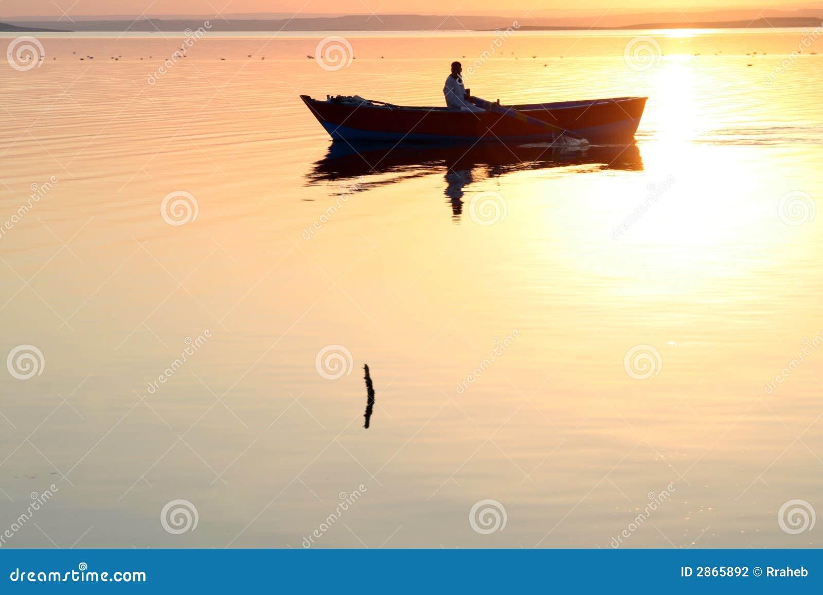 Água dourada da silhueta do barco