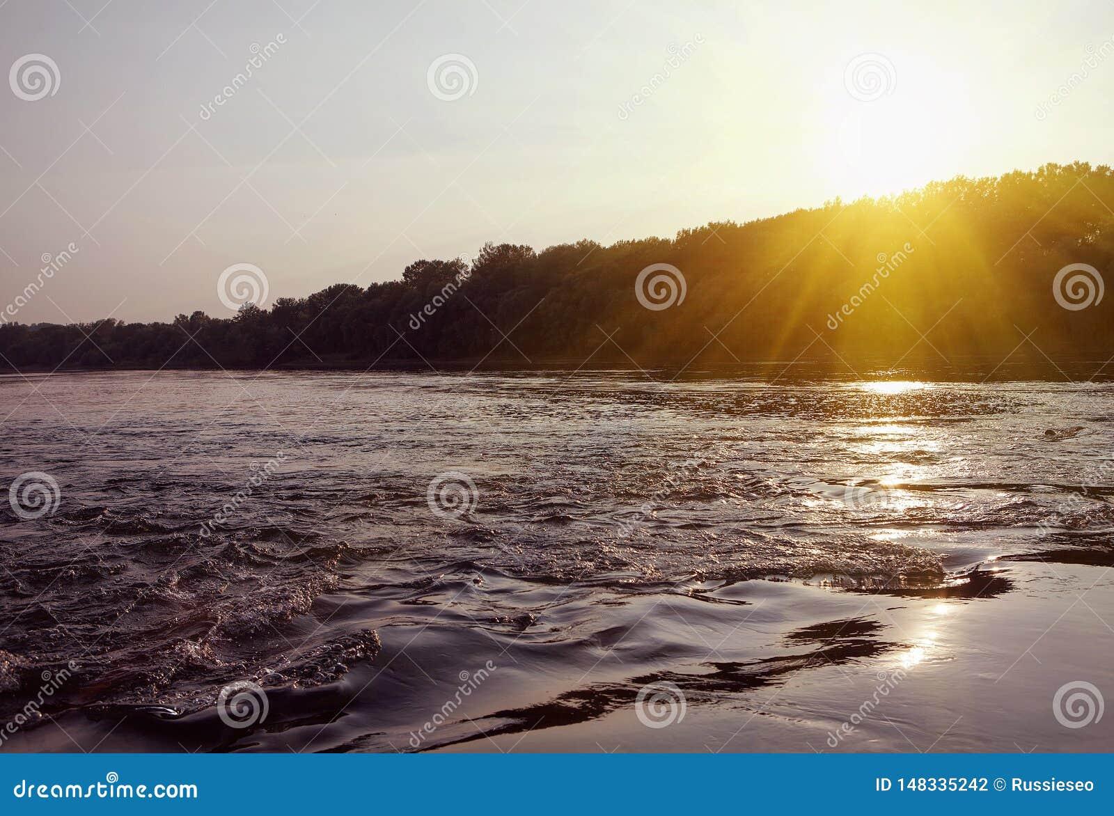 Água e por do sol de fluxo