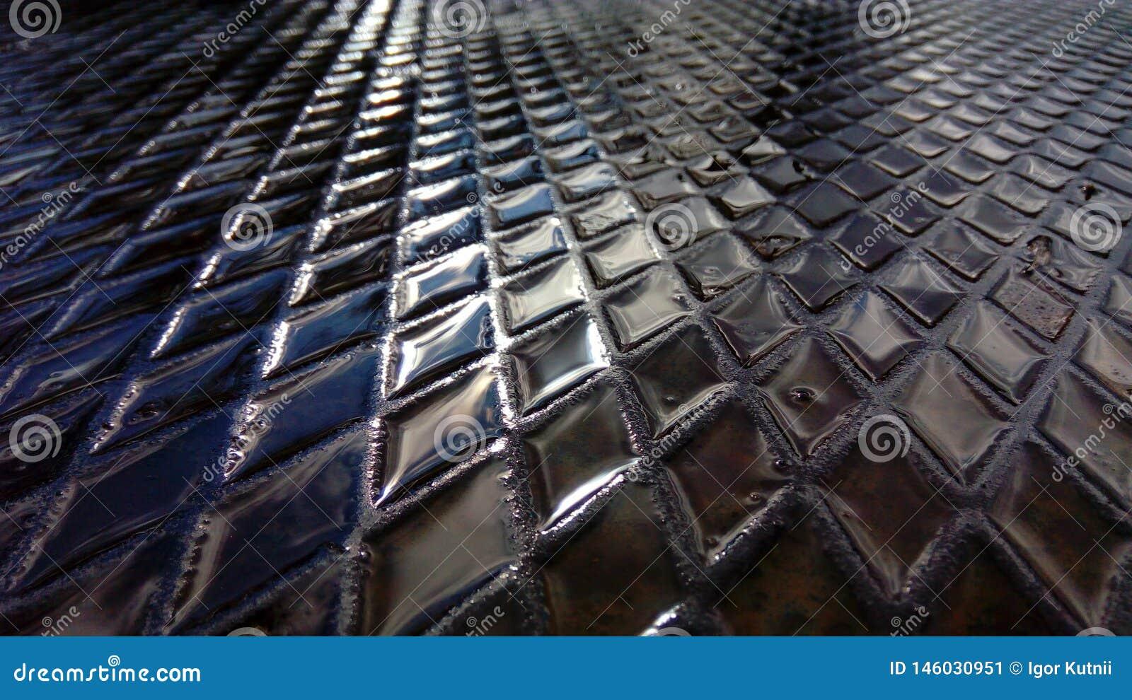Água nas pilhas de uma placa de metal textured As ruas da cidade moderna após a chuva