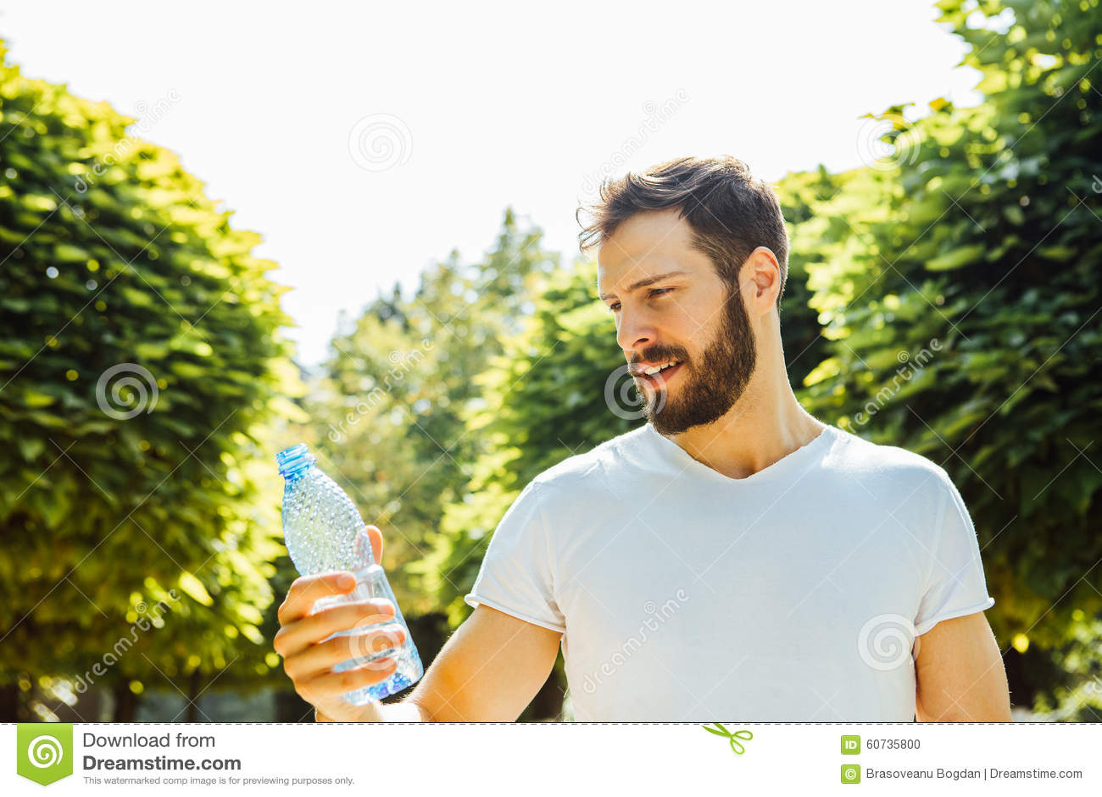 Água potável adulta do homem de uma garrafa fora