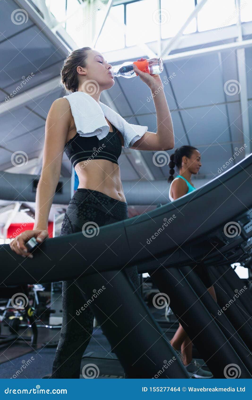 Água potável da mulher ao exercitar em uma escada rolante no fitness center