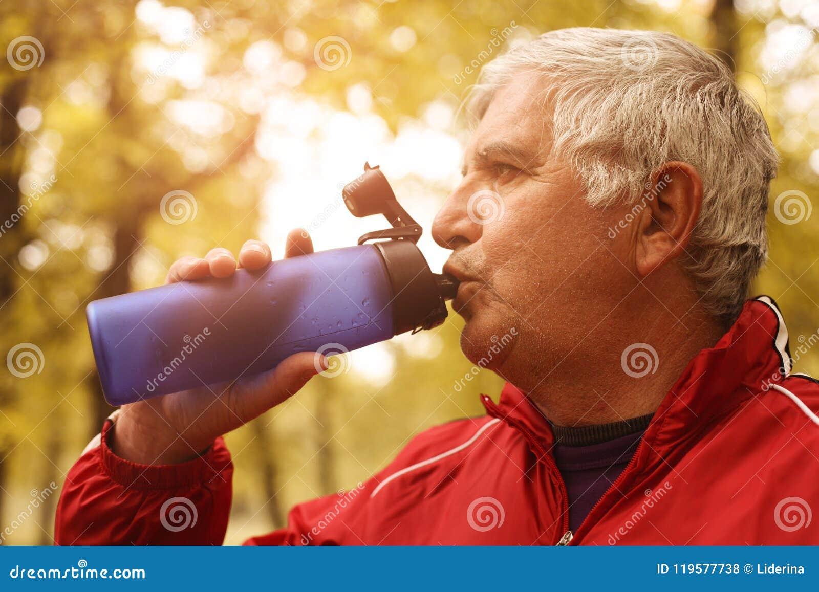 Água potável de meia idade do homem após o exercício