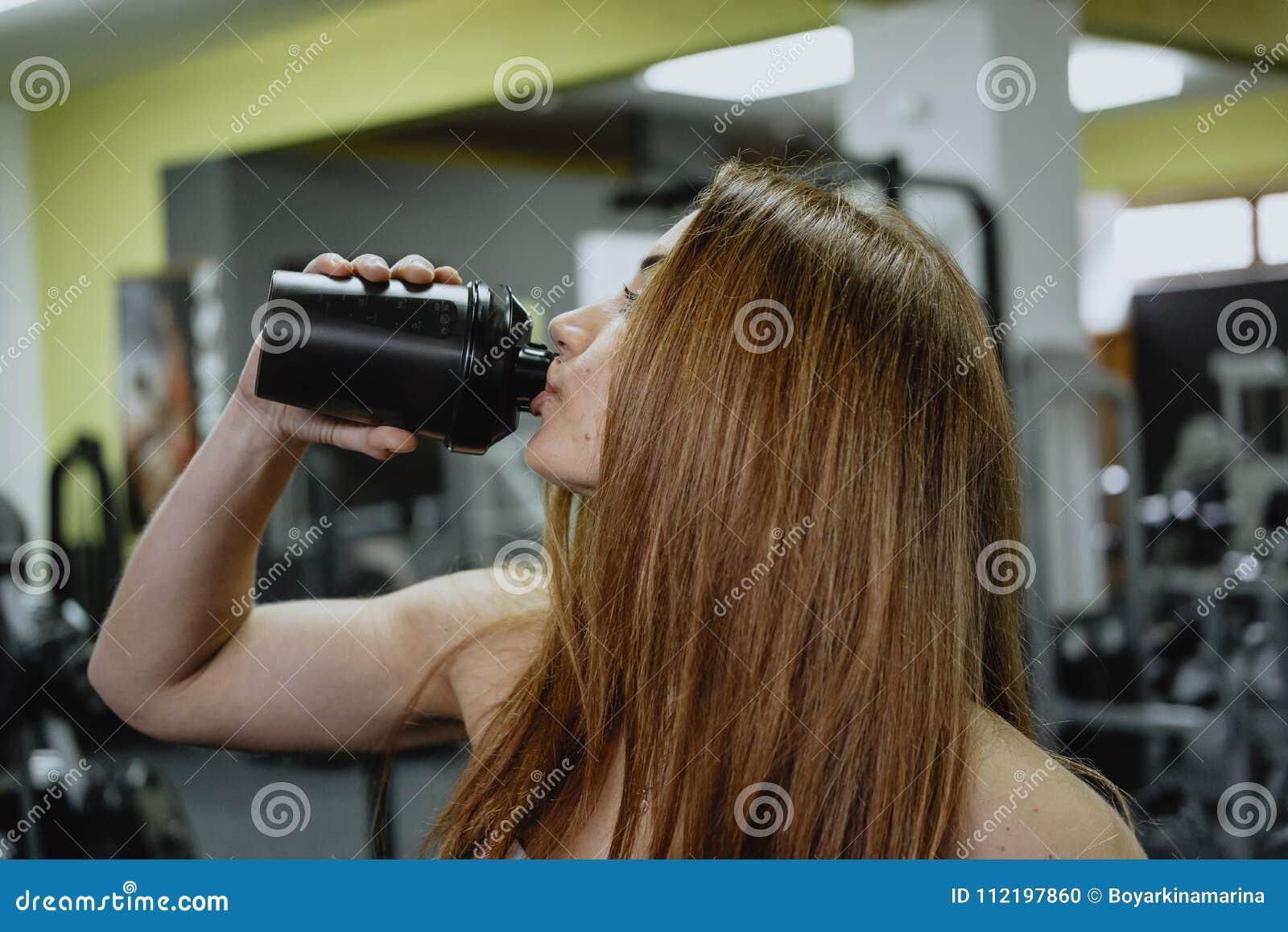 Água potável desportiva da jovem mulher ao dar certo no gym