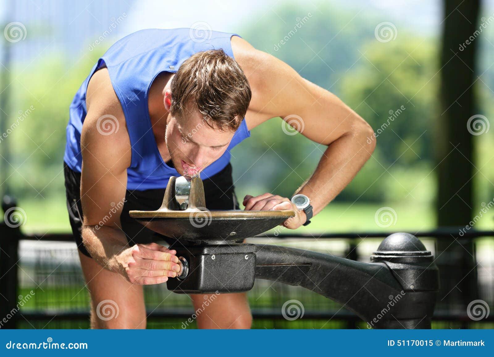 Água potável do homem do esporte da fonte do parque público