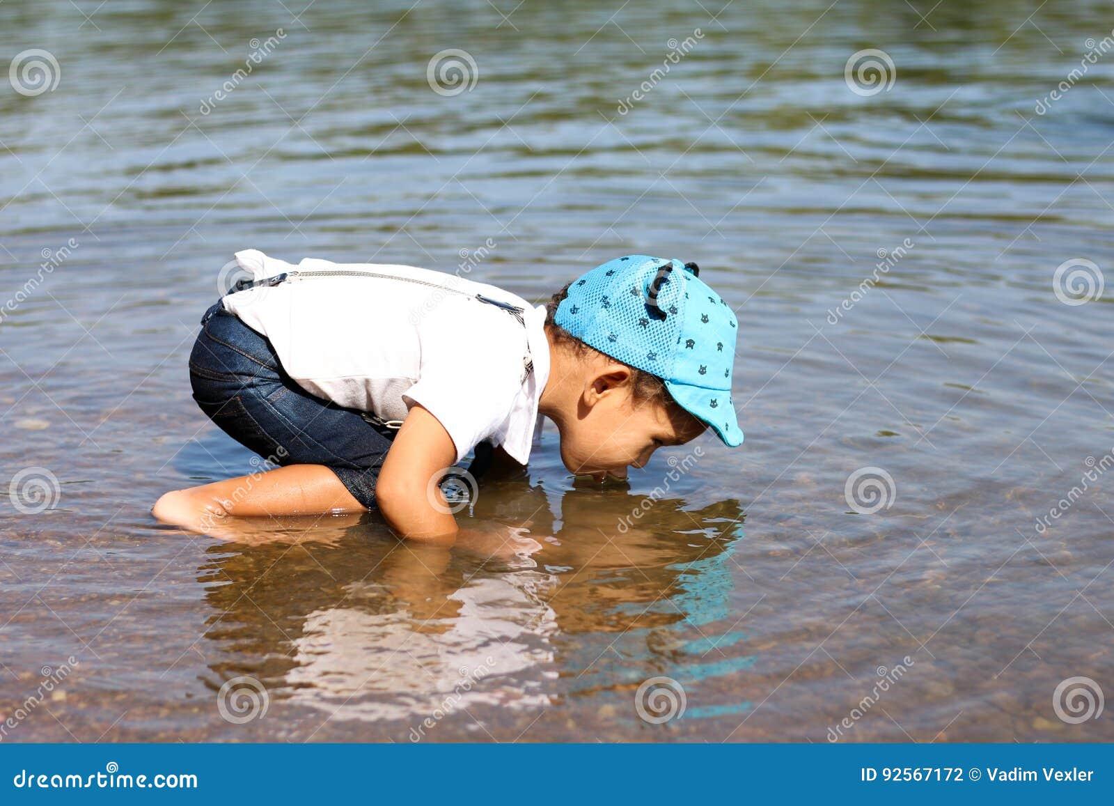 Água potável do rapaz pequeno do rio