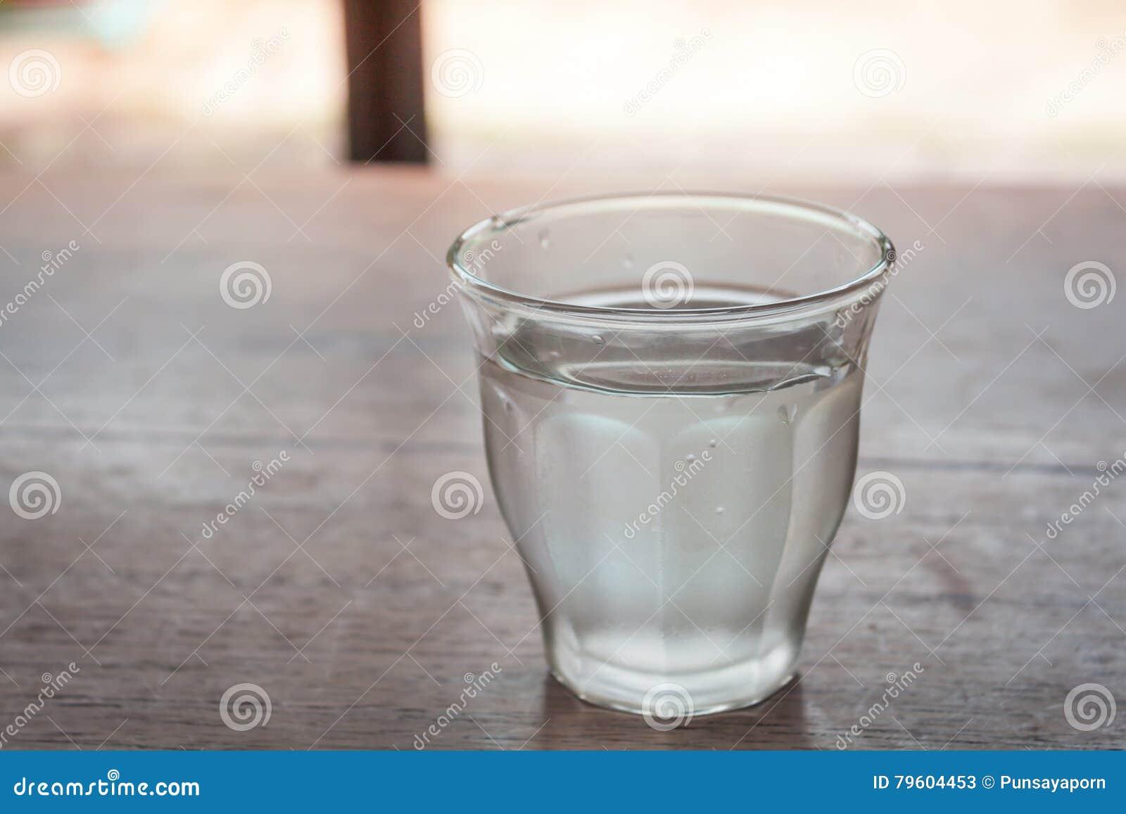 Água potável em um vidro na tabela de madeira