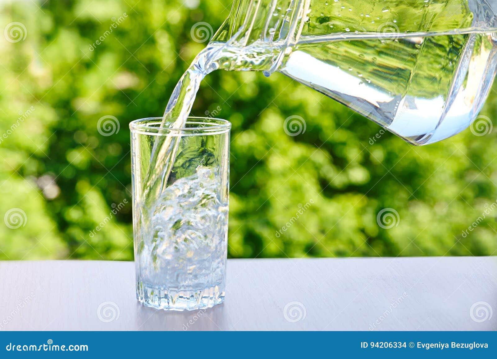 A água potável limpa é derramada de um jarro em um vidro