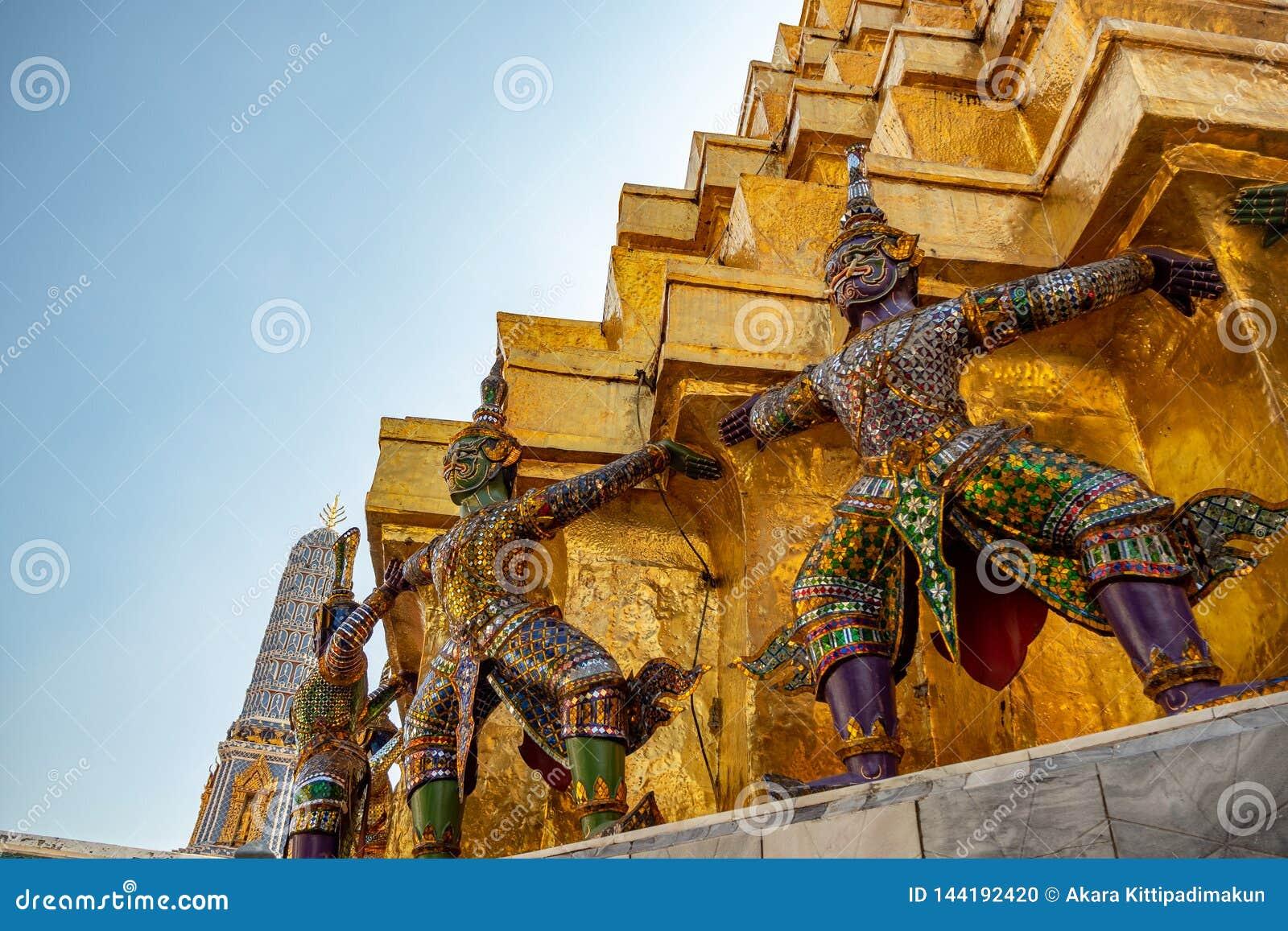 Ángulo bajo de estatuas gigantes en la base de la pagoda de oro en templo real en palacio magnífico con el fondo claro de cielo a