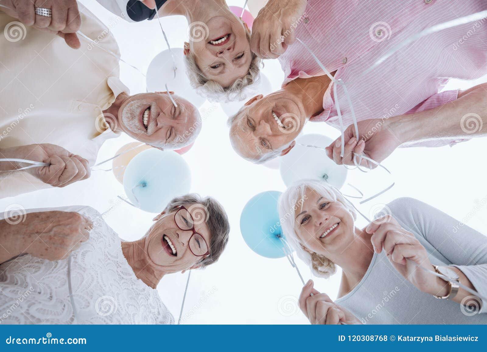 Ángulo bajo de la gente mayor feliz en el círculo con los globos