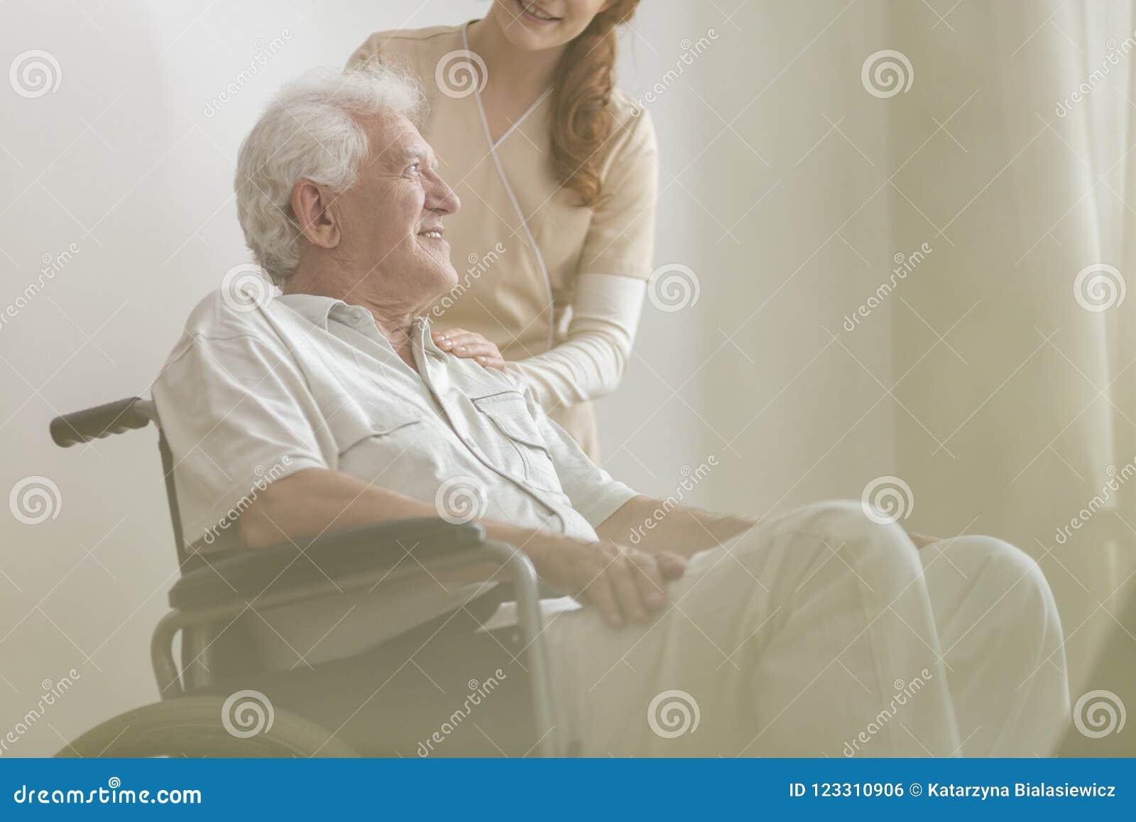 Ángulo bajo en la sonrisa y hombre mayor discapacitado feliz en un wheelch