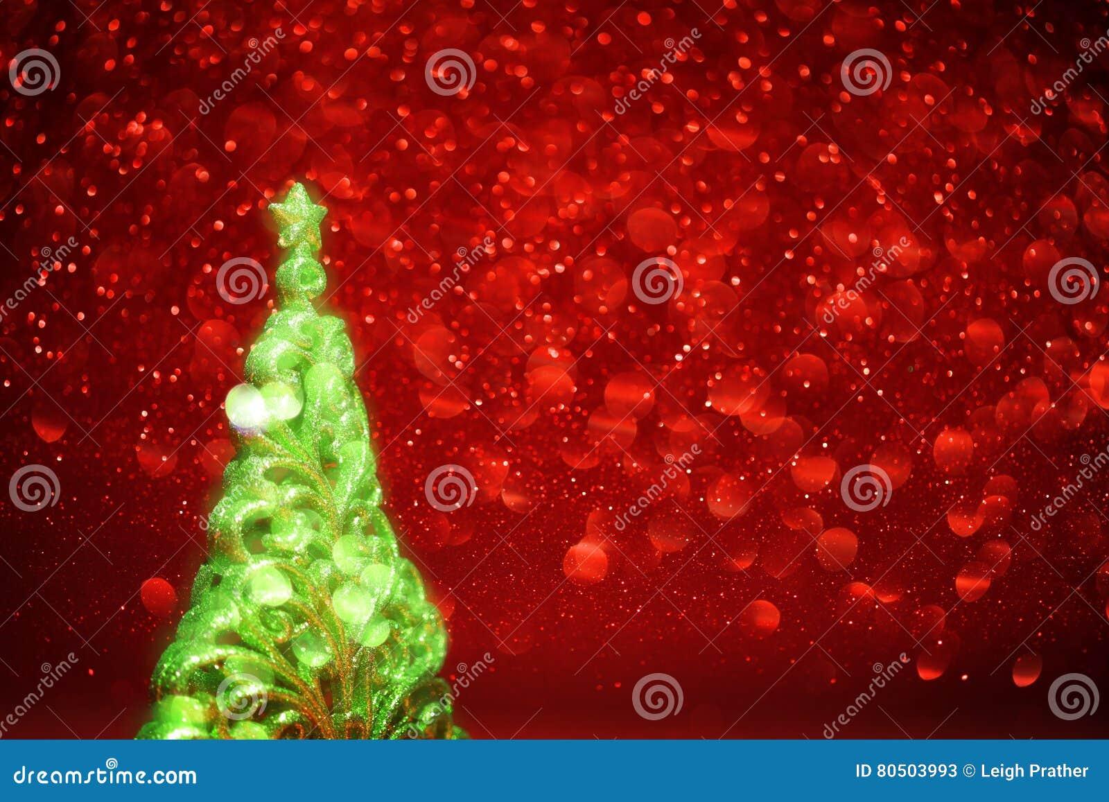 Árbol de navidad que brilla intensamente y backgro abstracto de las luces rojas