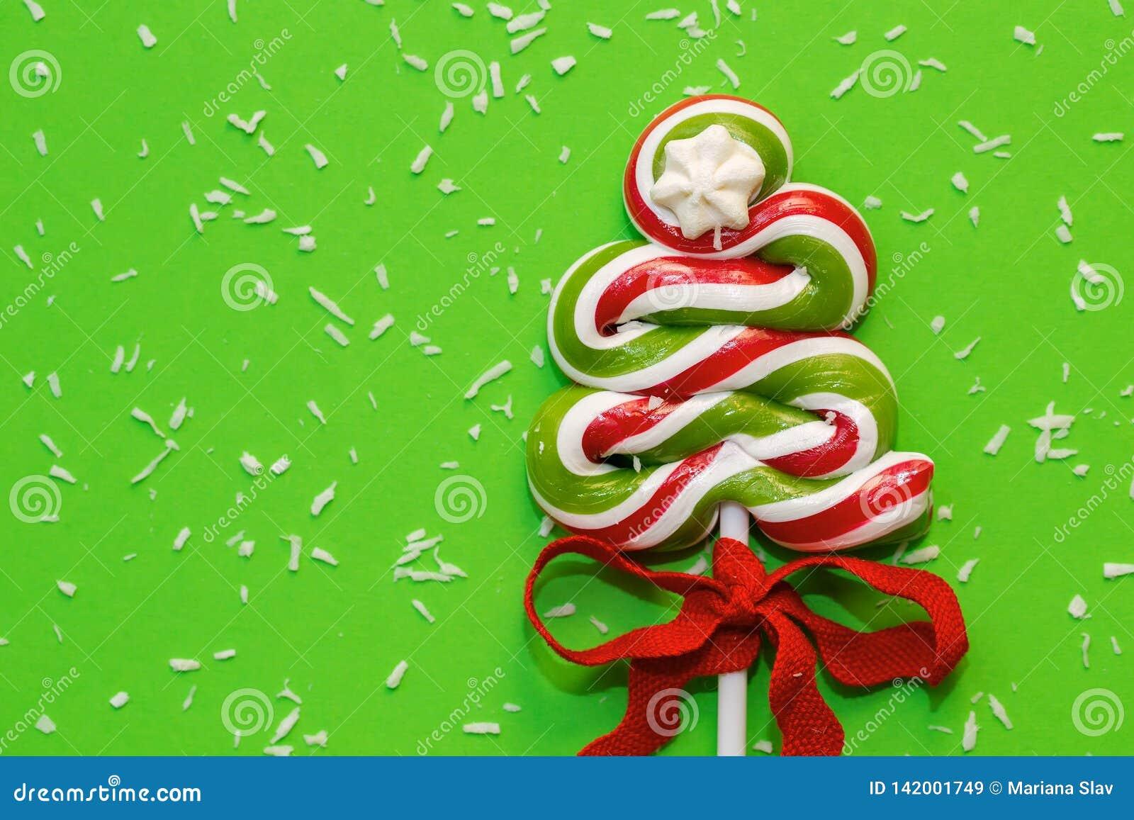 Árbol de navidad y nieve verdes - coco desecado del caramelo - delante del fondo verde Dejáis le nevar
