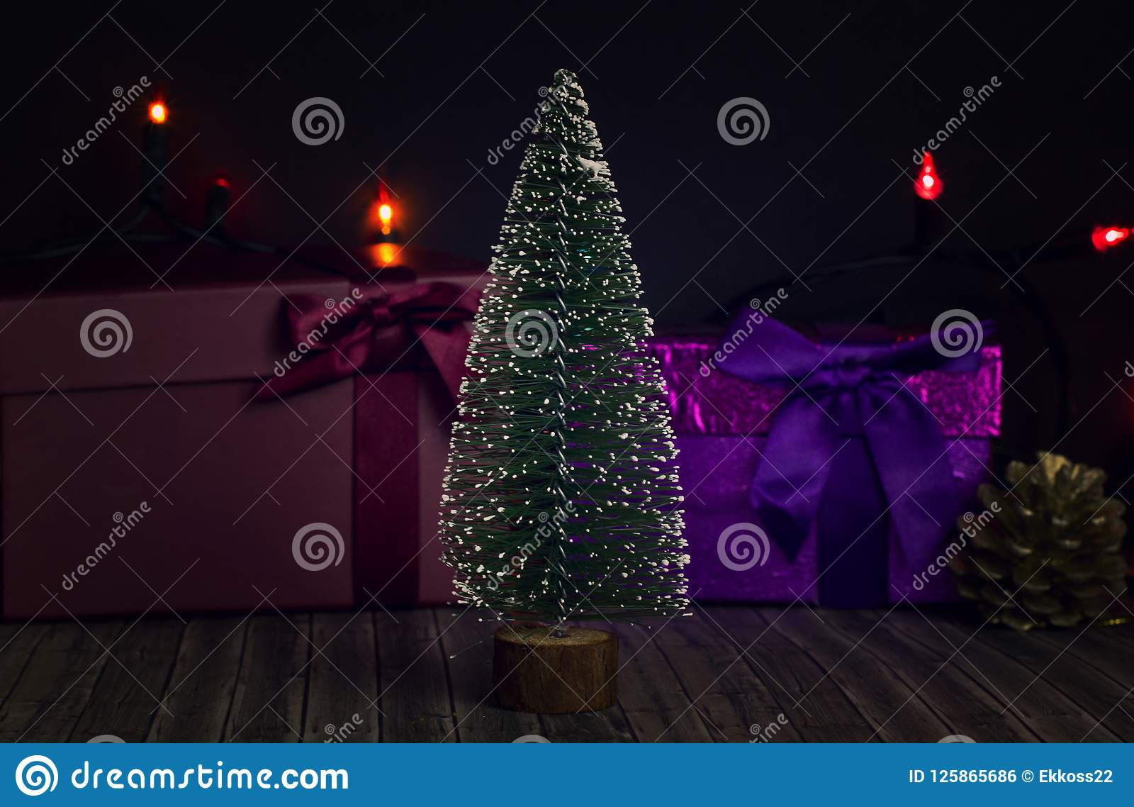 Árbol del Año Nuevo en un fondo oscuro con las cajas de regalo