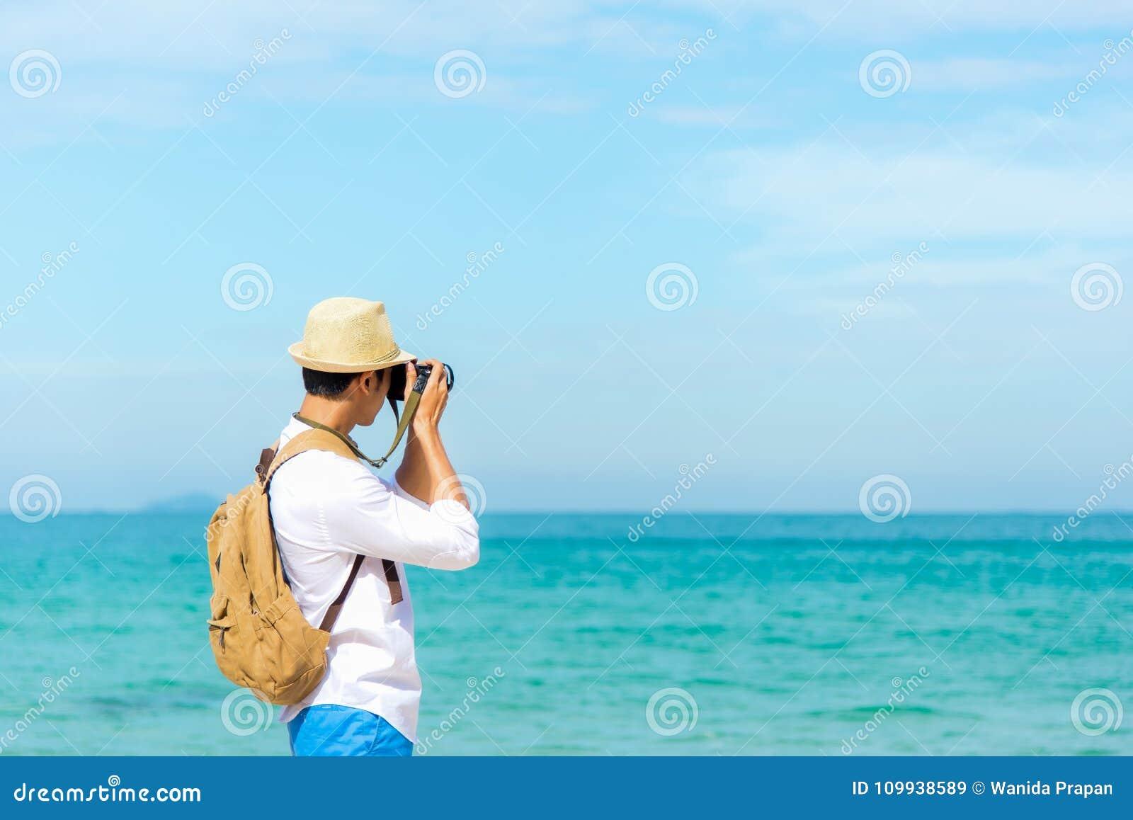 Árbol en campo Hombre joven asiático turístico caucásico sonriente feliz que sostiene la cámara