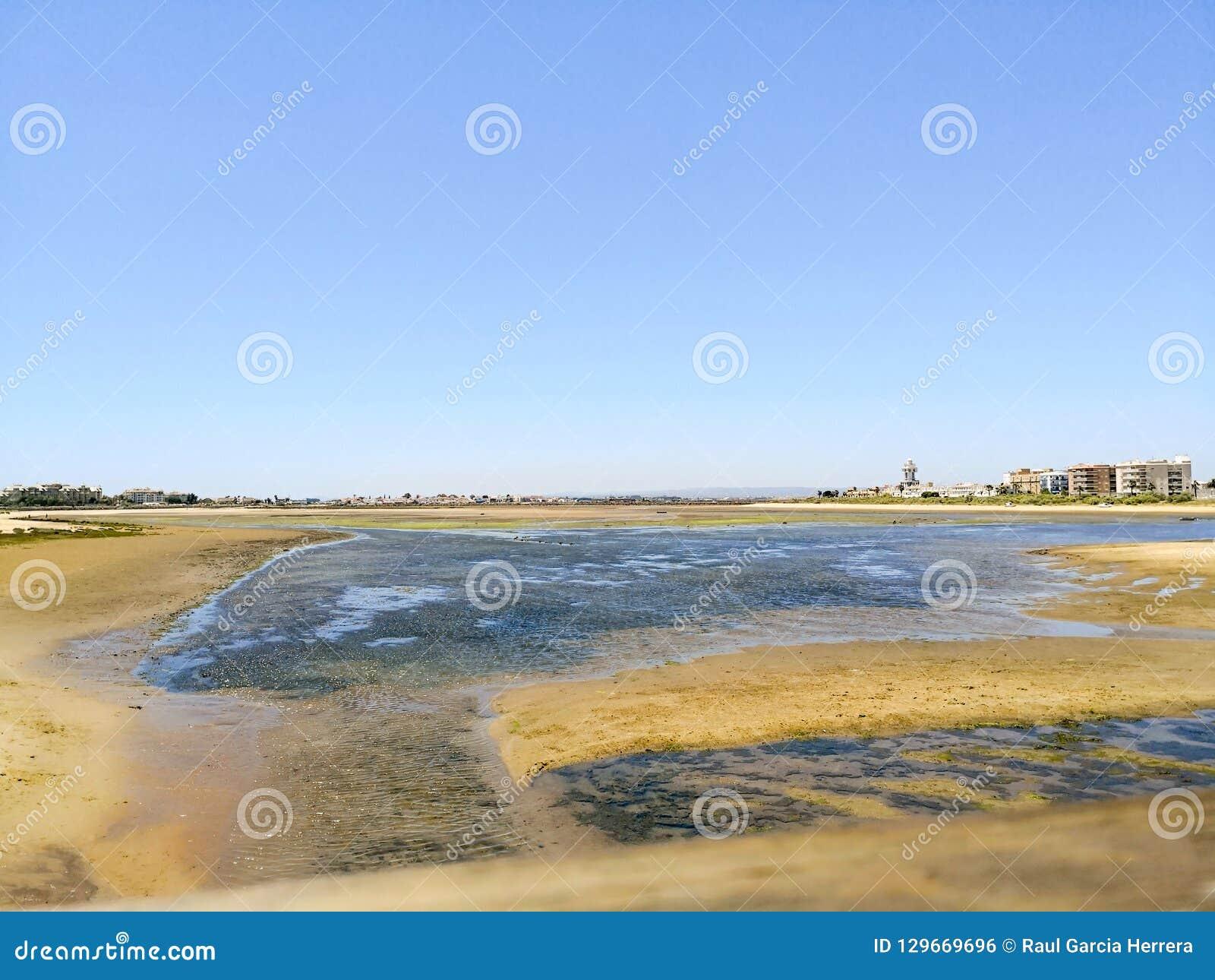 Área do marisco ao lado da praia de Cristina do isla, Costa de la Luz, Huelva, Espanha Praia de Cantil no fundo