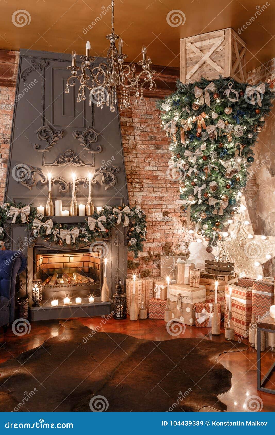 Árvore alternativa de cabeça para baixo no teto Decoração home do inverno Interior moderno do sótão com chaminé e parede de tijol