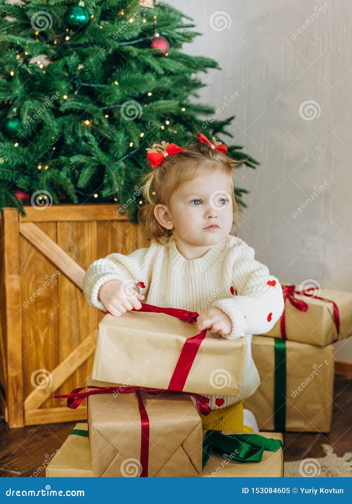 A árvore de Natal da caixa de presente da criança desata fitas