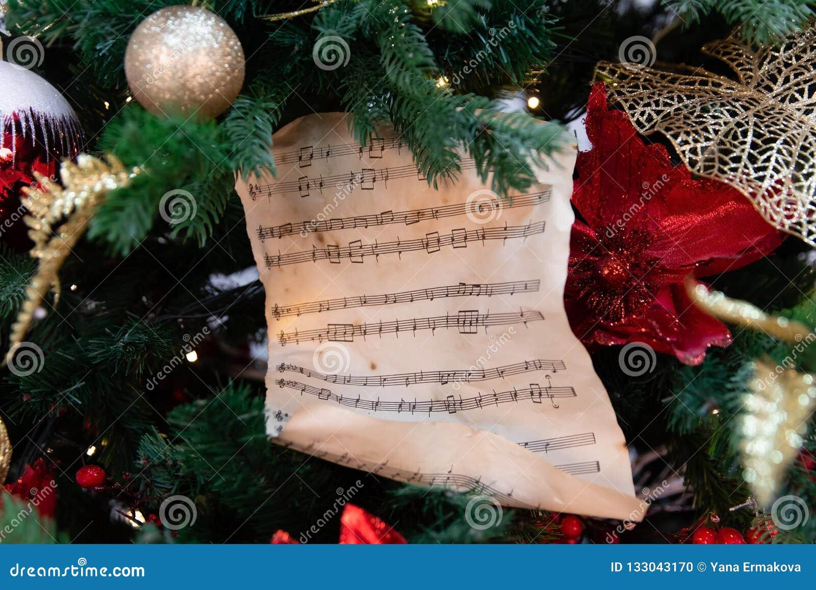 Árvore de Natal decorada com brinquedos, luzes e partitura
