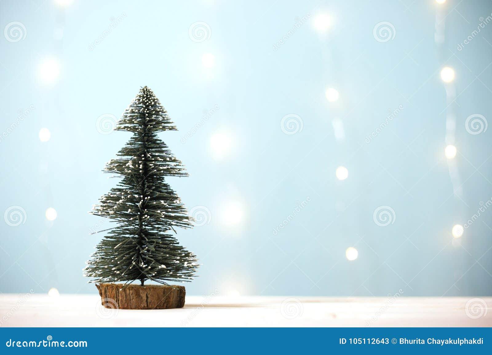 Árvore de Natal diminuta na tabela de madeira sobre a luz do bokeh do borrão - fundo azul