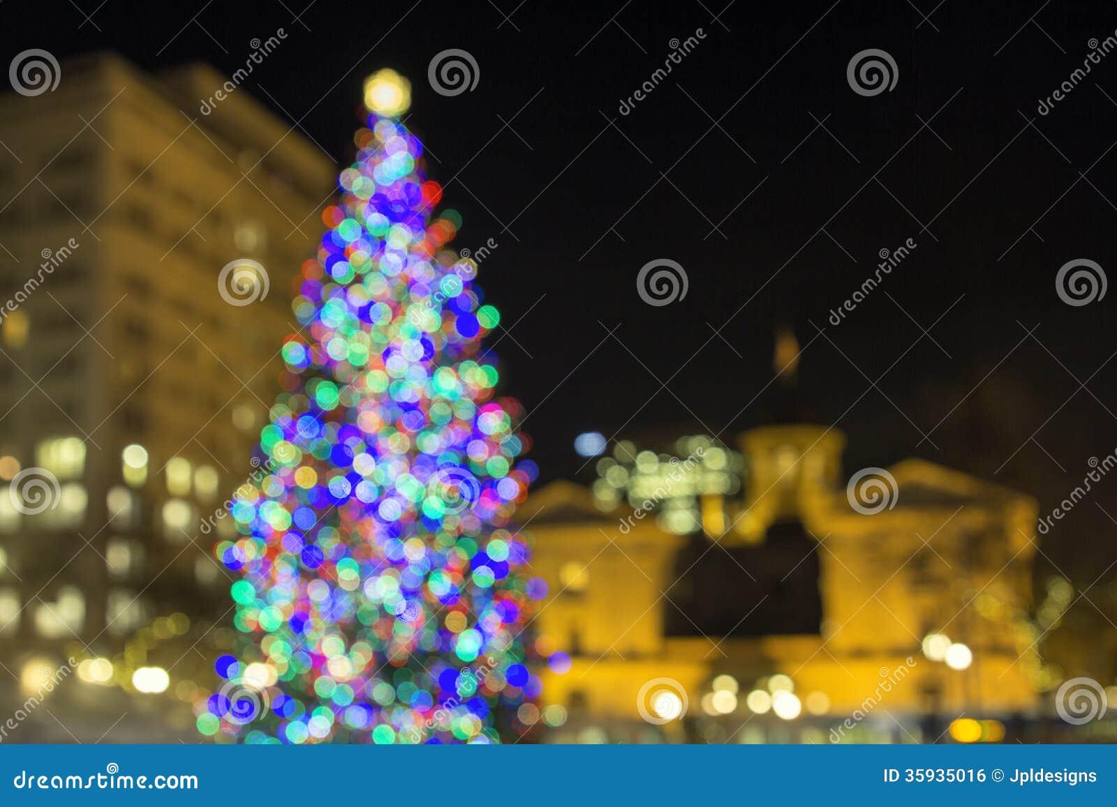 Árvore de Natal em luzes pioneiras de Bokeh do quadrado do tribunal