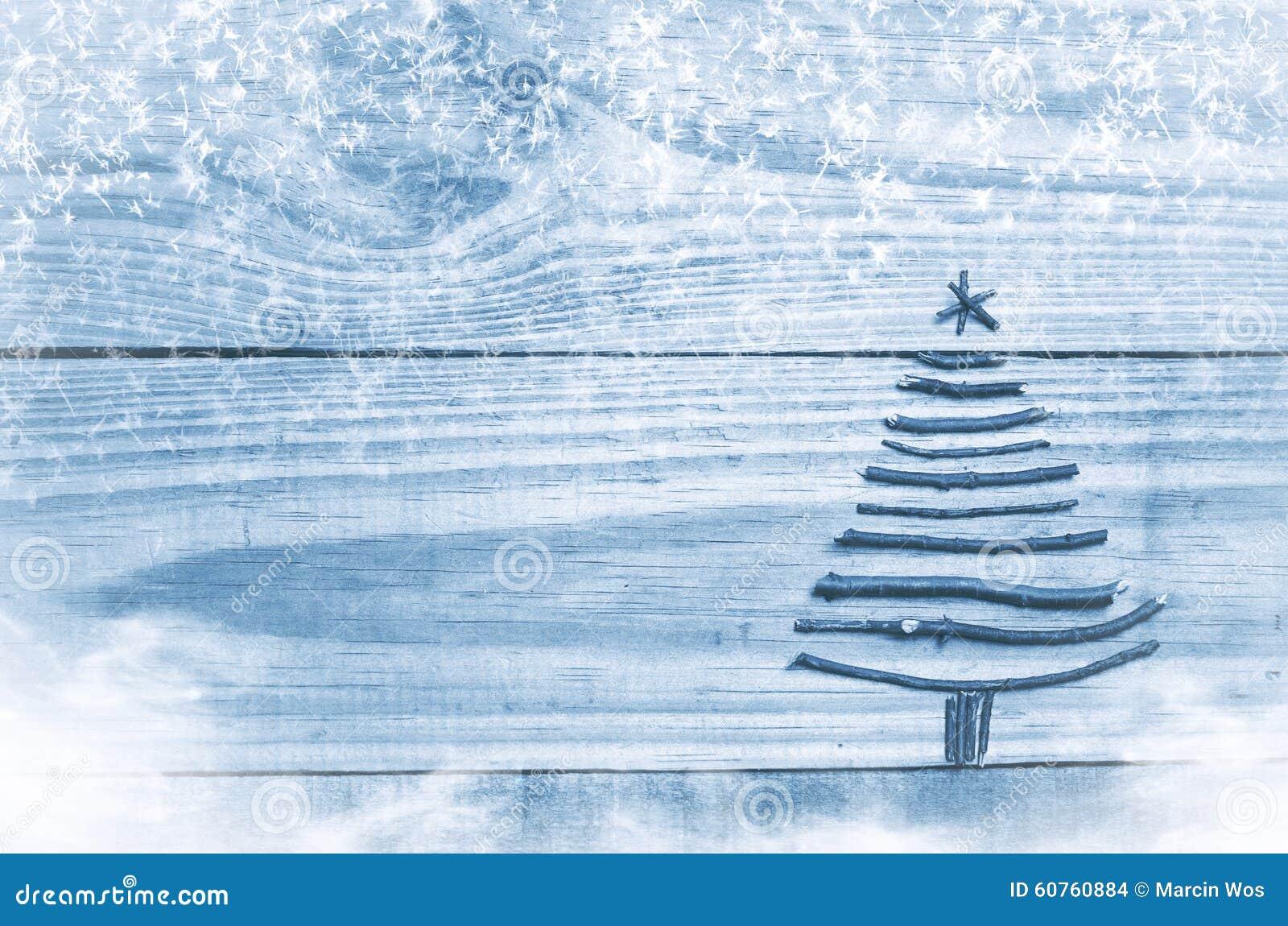 Árvore de Natal feita das varas secas no fundo de madeira, azul Imagem da neve e das oposições da neve Ornamento da árvore de Nat