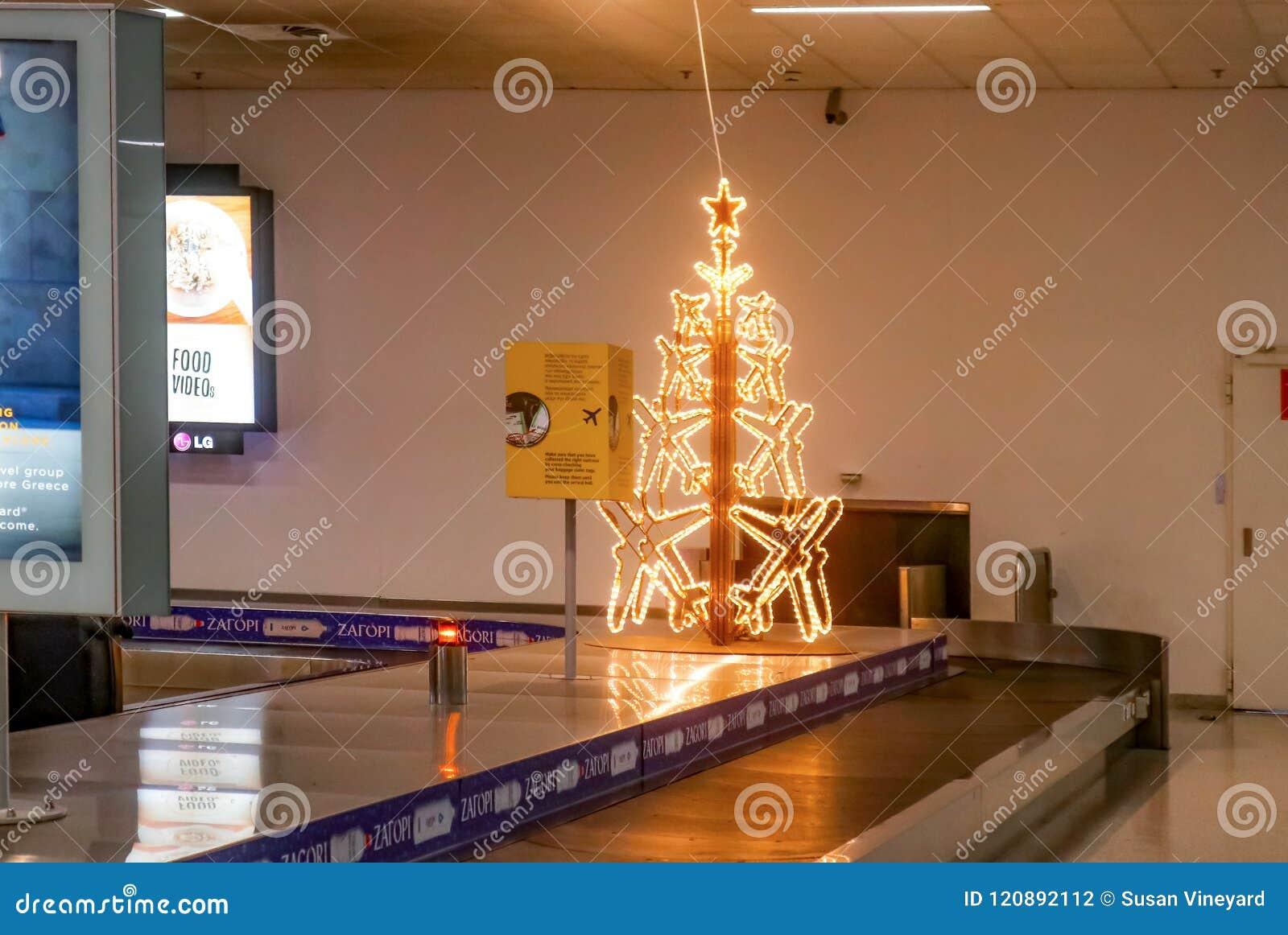 Árvore de Natal iluminada do avião na correia transportadora da bagagem no aeroporto tarde quase abandonado na noite no Ch