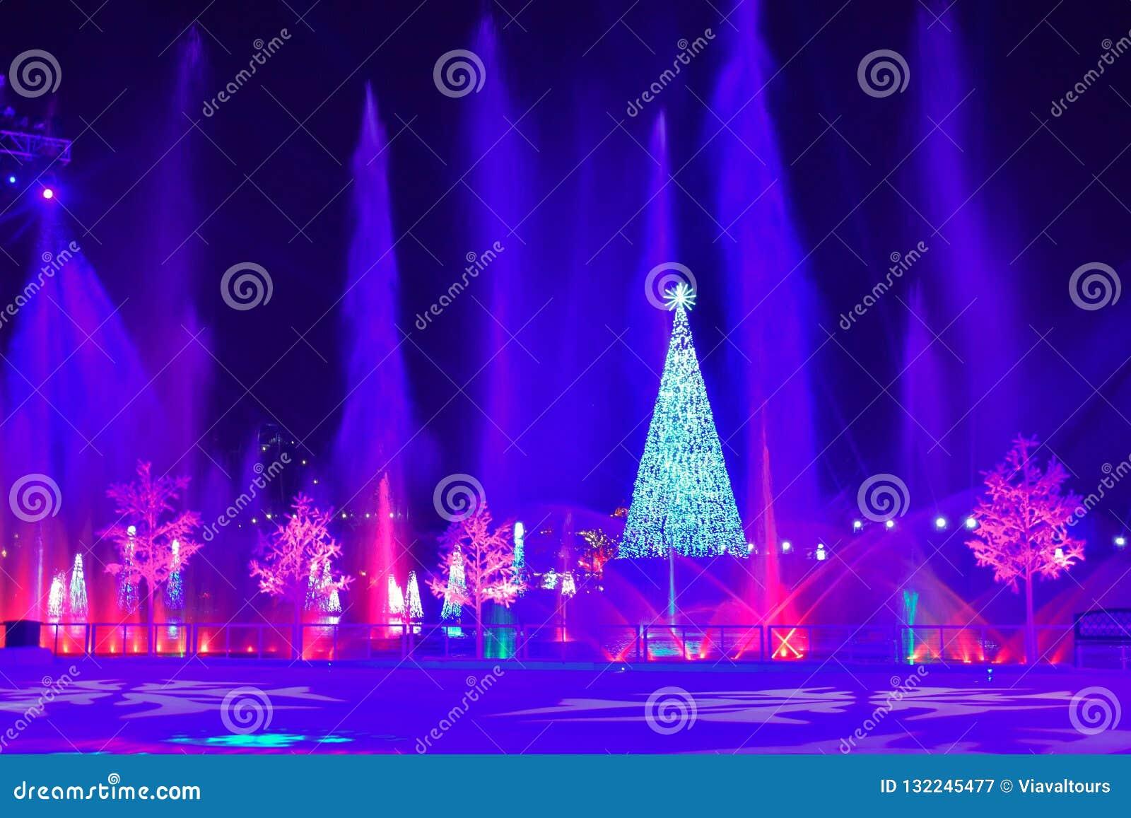 Árvore de Natal iluminada, jatos da água e árvores coloridas dos feriados na noite na área internacional da movimentação