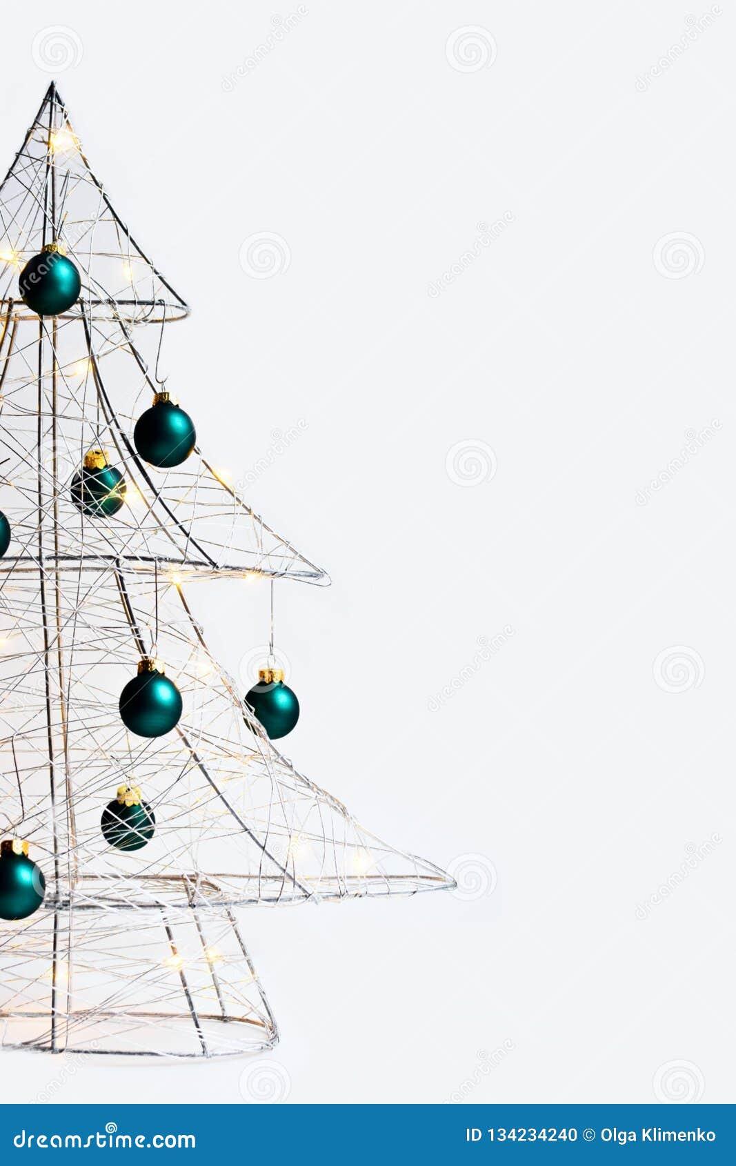 Árvore de Natal moderna feita do fio de metal de prata, envolvida em uma festão de incandescência e decorada com bolas verdes