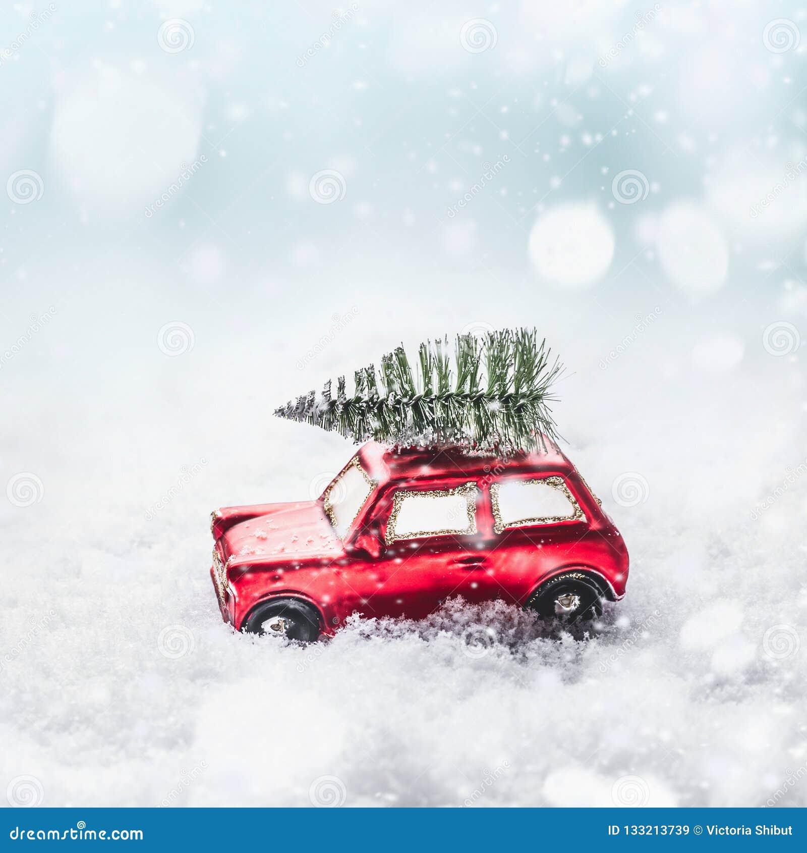 Árvore de Natal no carro retro do brinquedo vermelho na neve, através da terra nevado da maravilha do inverno com queda de neve e